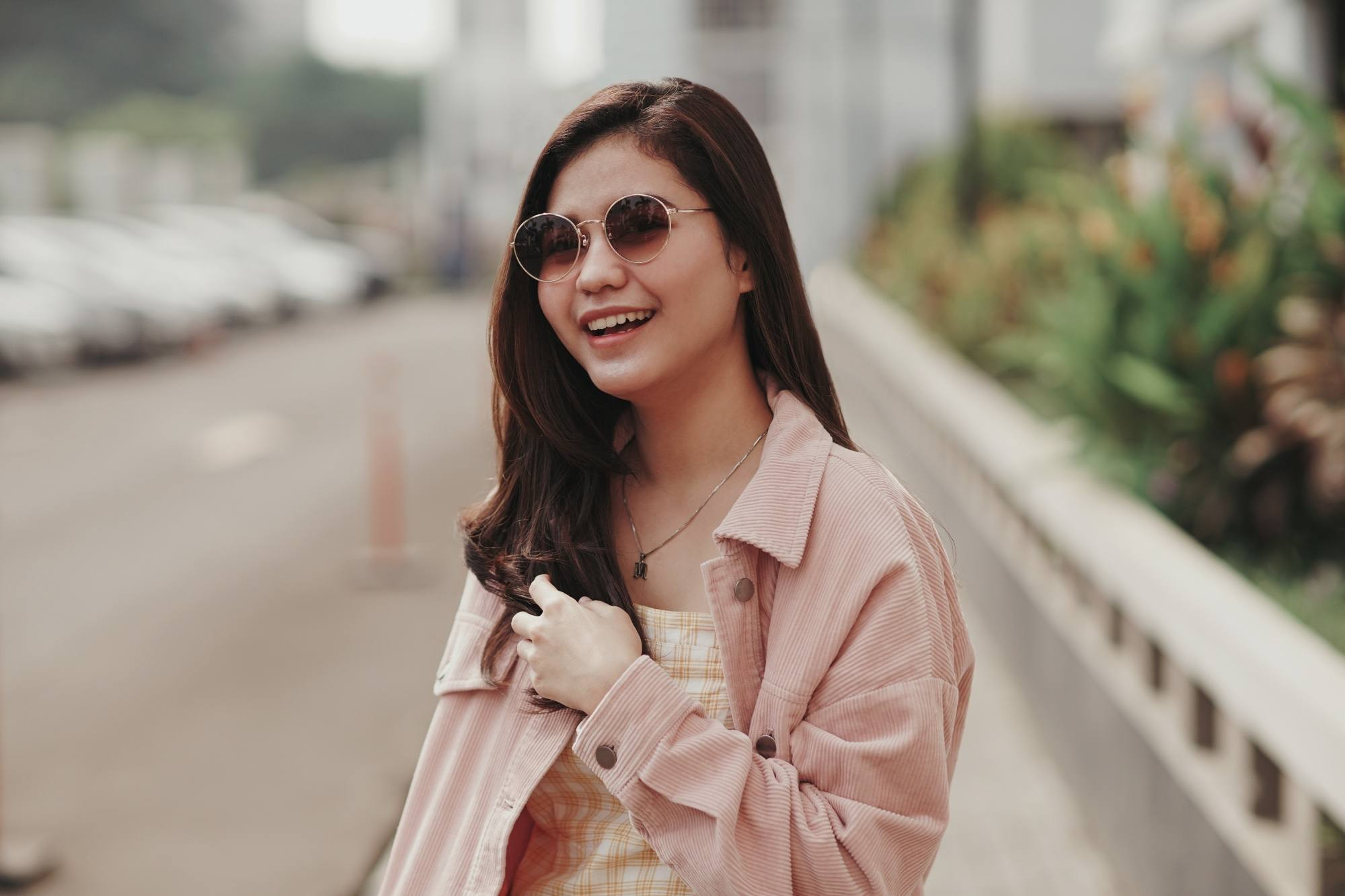 Hair Facts: Asian woman with long dark hair wearing shades smiling outdoors