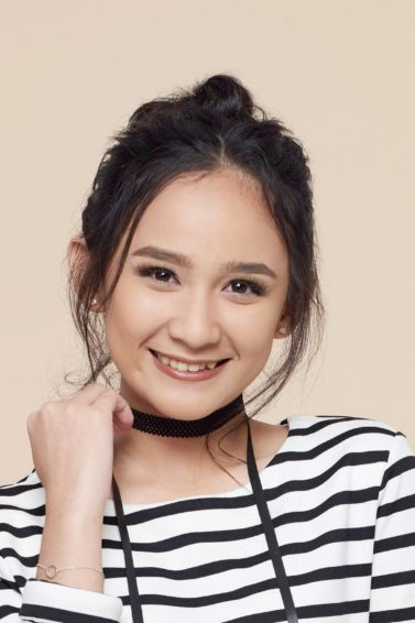 Hairstyles for thin hair: Closeup shot of an Asian girl wearing a striped long-sleeved shirt with dark hair in a messy bun