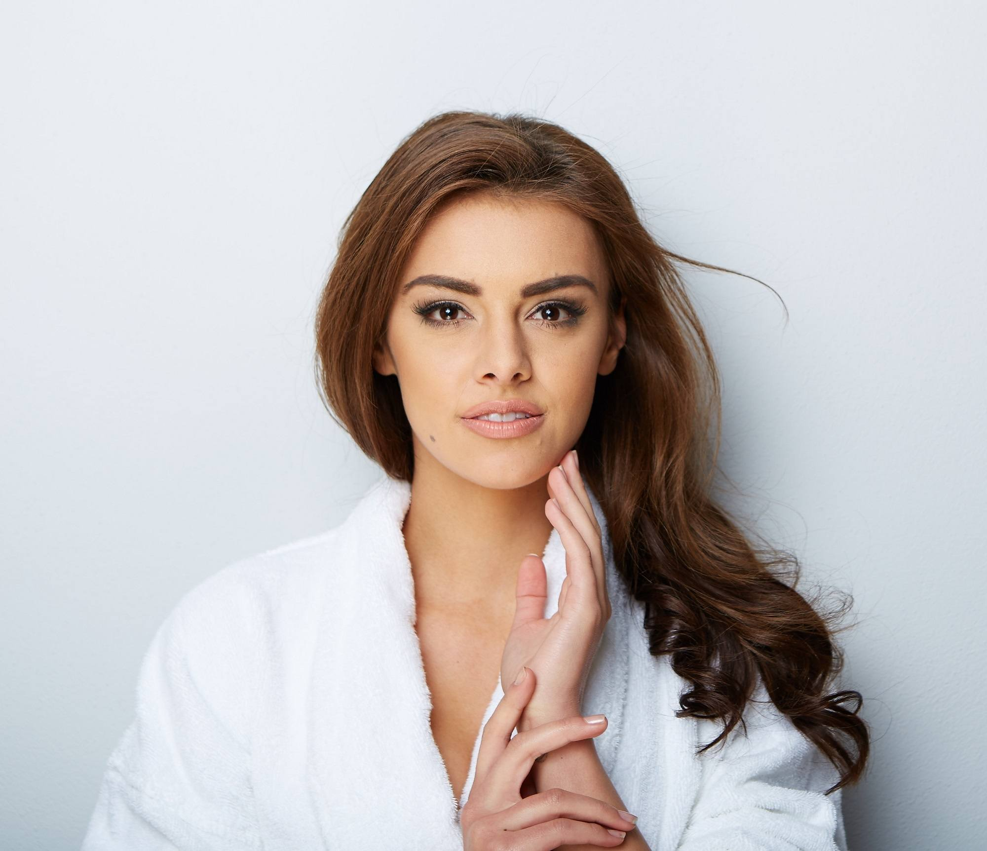 Remedies for dry hair: Closeup shot of woman with long brown hair wearing a white robe