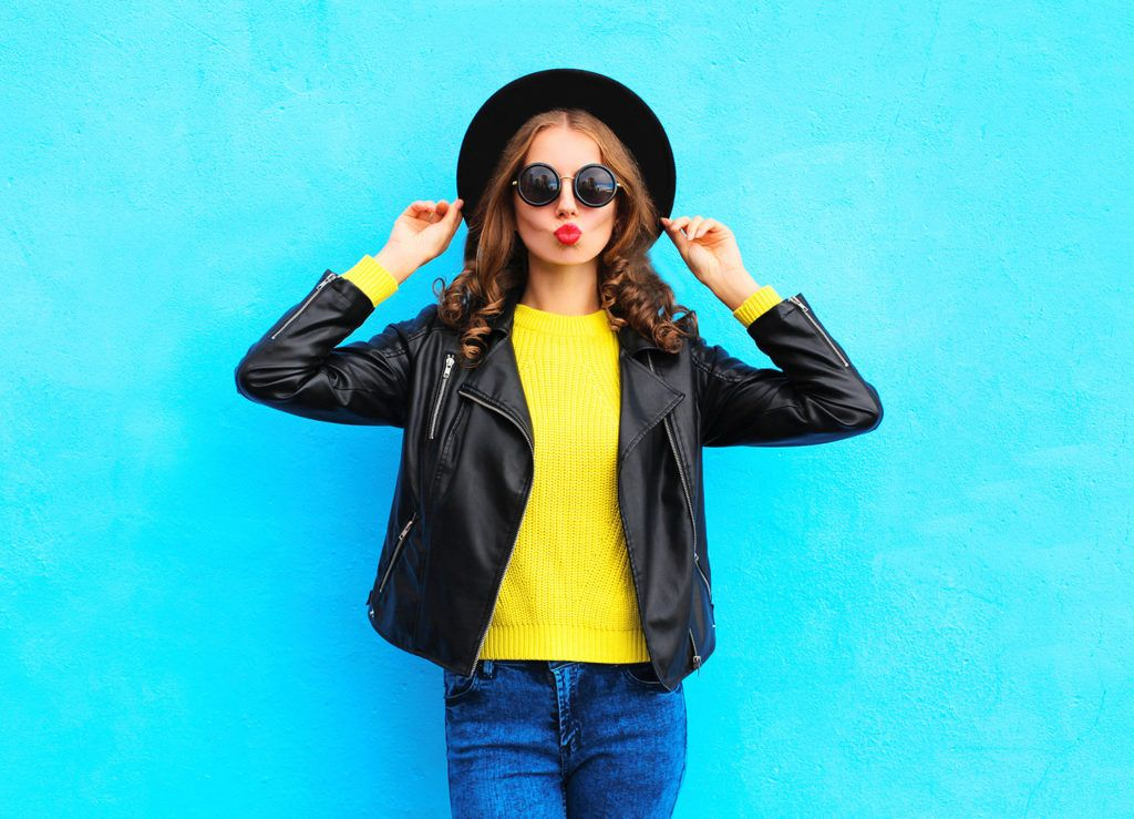 Fashion pretty young woman wearing a black rock style clothes over colorful blue background