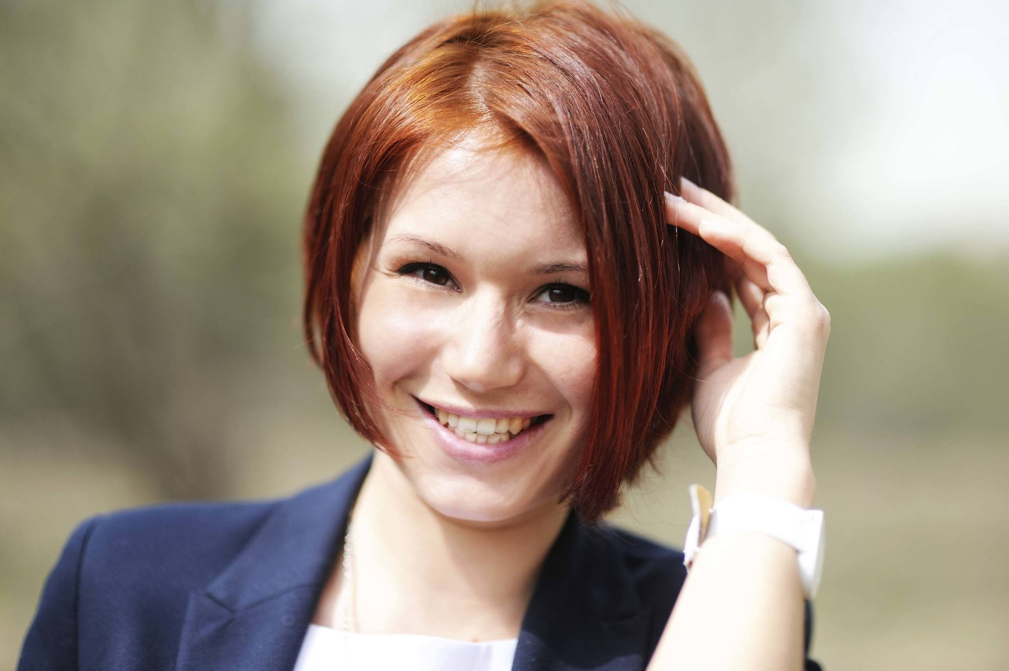 Short hair for round face: Closeup shot of a woman with short red hair smiling outdoors
