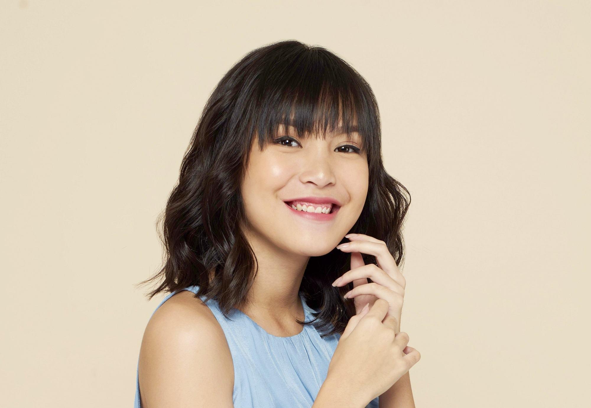 Shoulder length haircuts: Closeup shot of an Asian woman with dark shoulder length hair with bangs