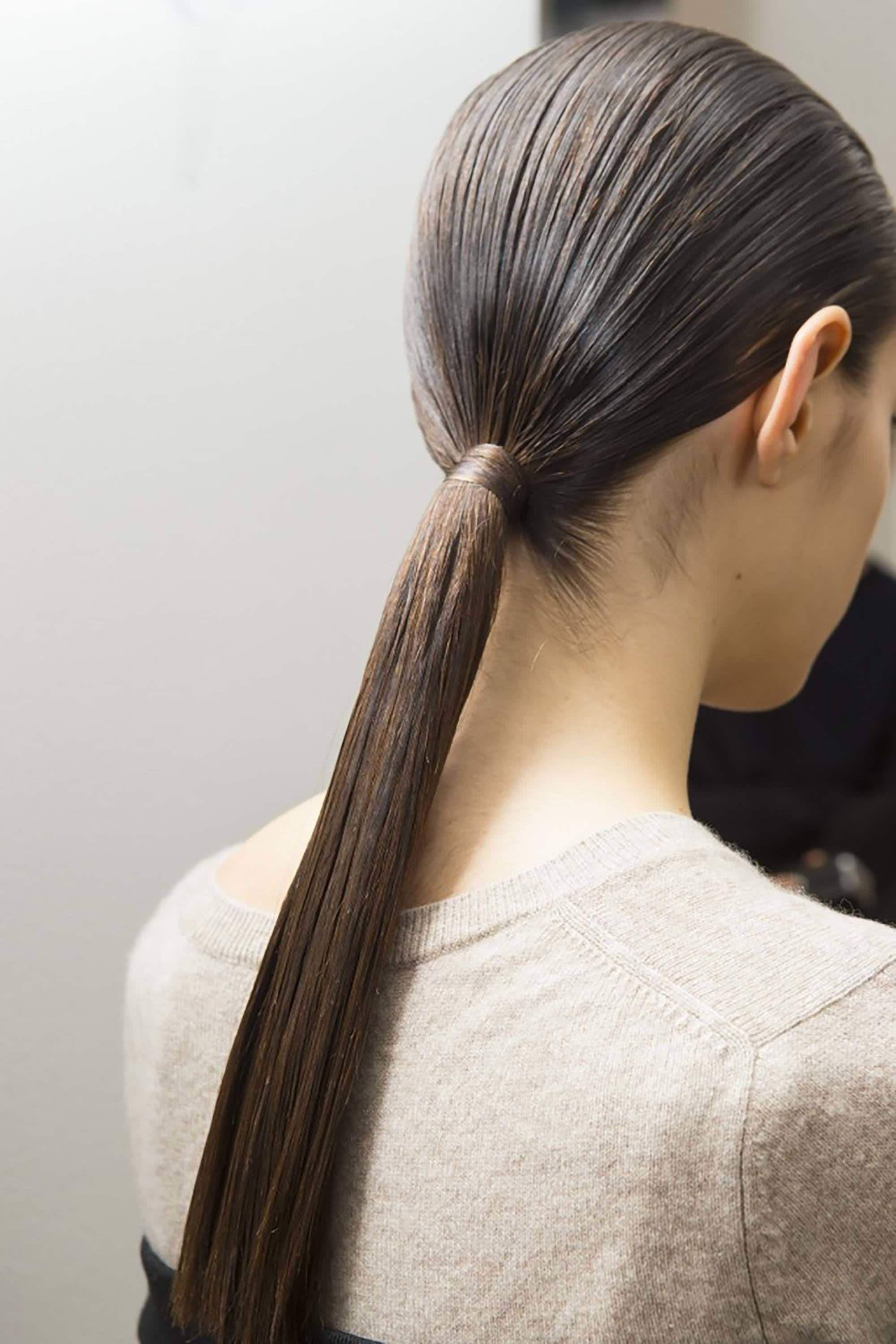 brunette woman with long, low ponytail