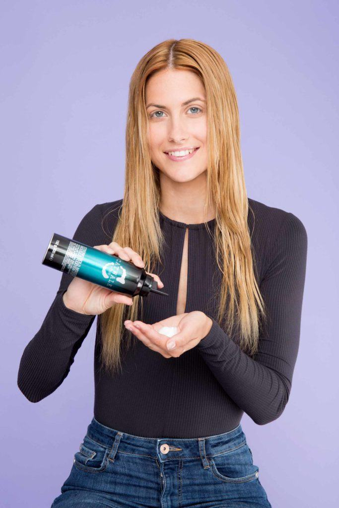 blonde girl applying with hair mousse on palm