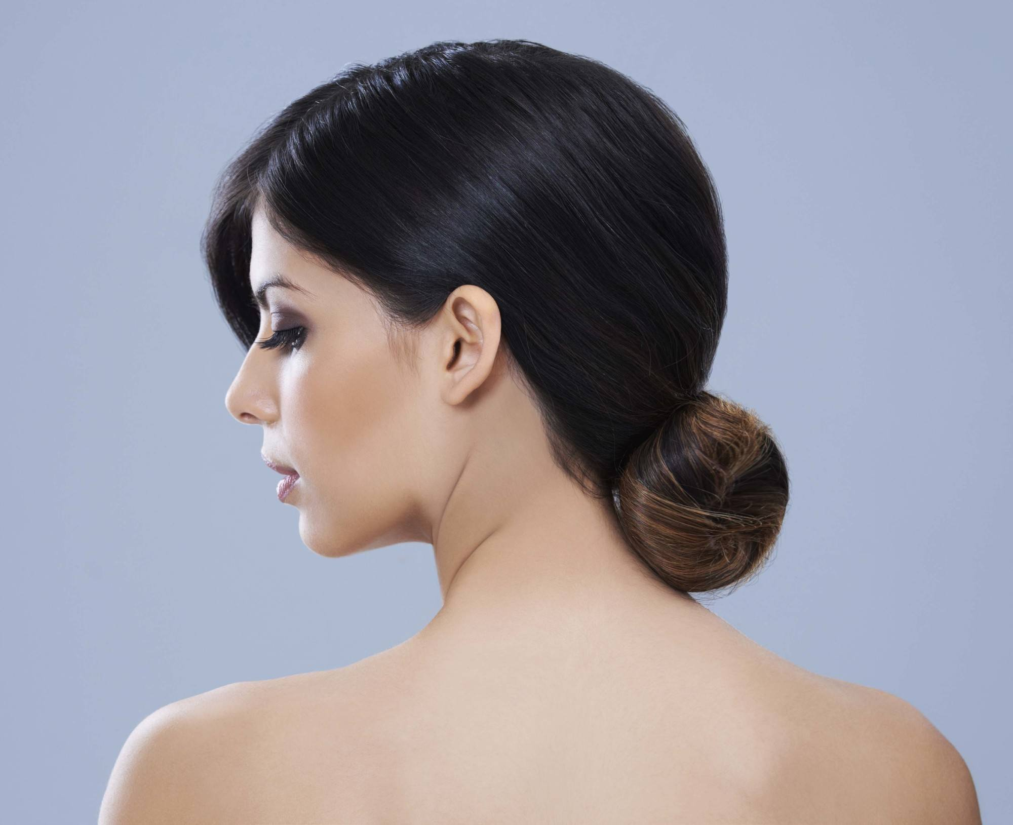 Easy commuter-friendly hairstyles: A brunette woman with her hair in a low bun
