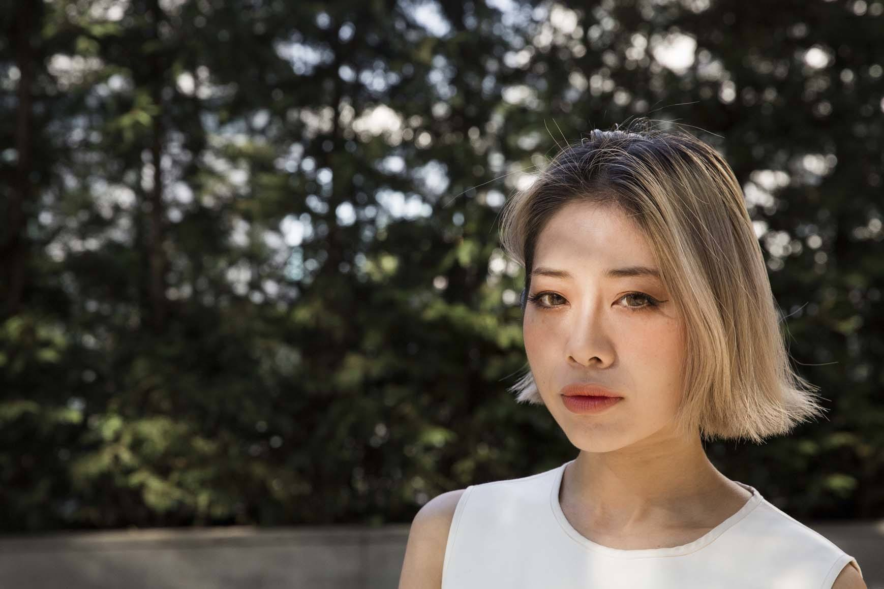 Hair color for fair skin: Asian woman with golden short hair and fair skin with trees in the background