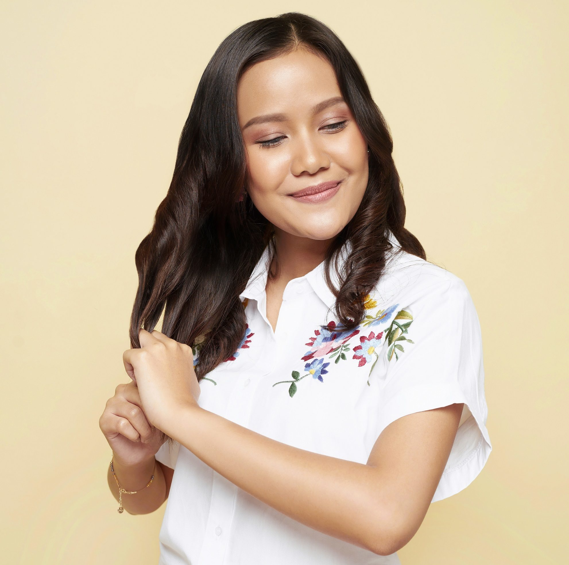 How to use leave-in conditioner: Asian woman applying product to her shoulder-length brown hair