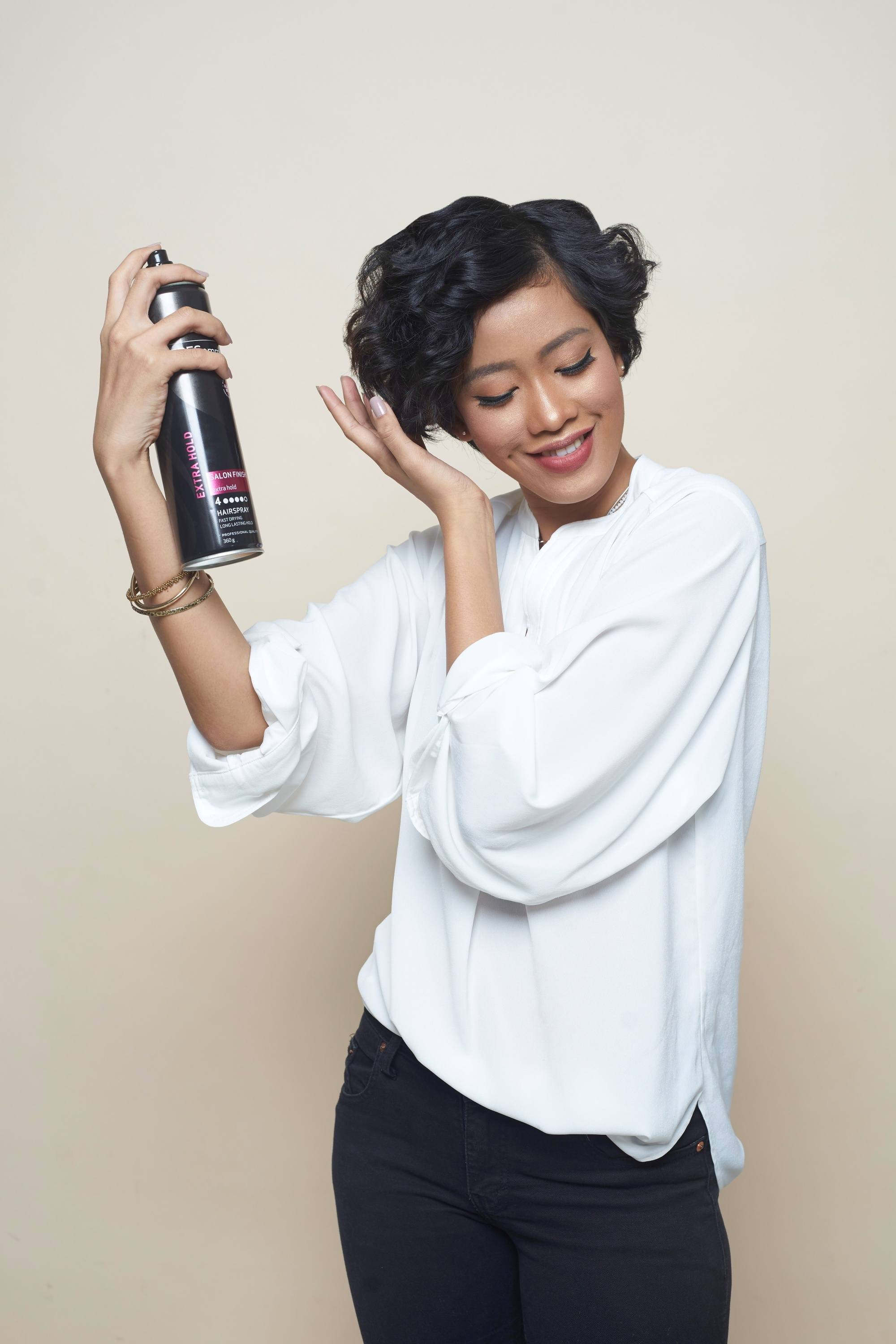 Hair spray guide: Asian woman spraying on her short curly hair