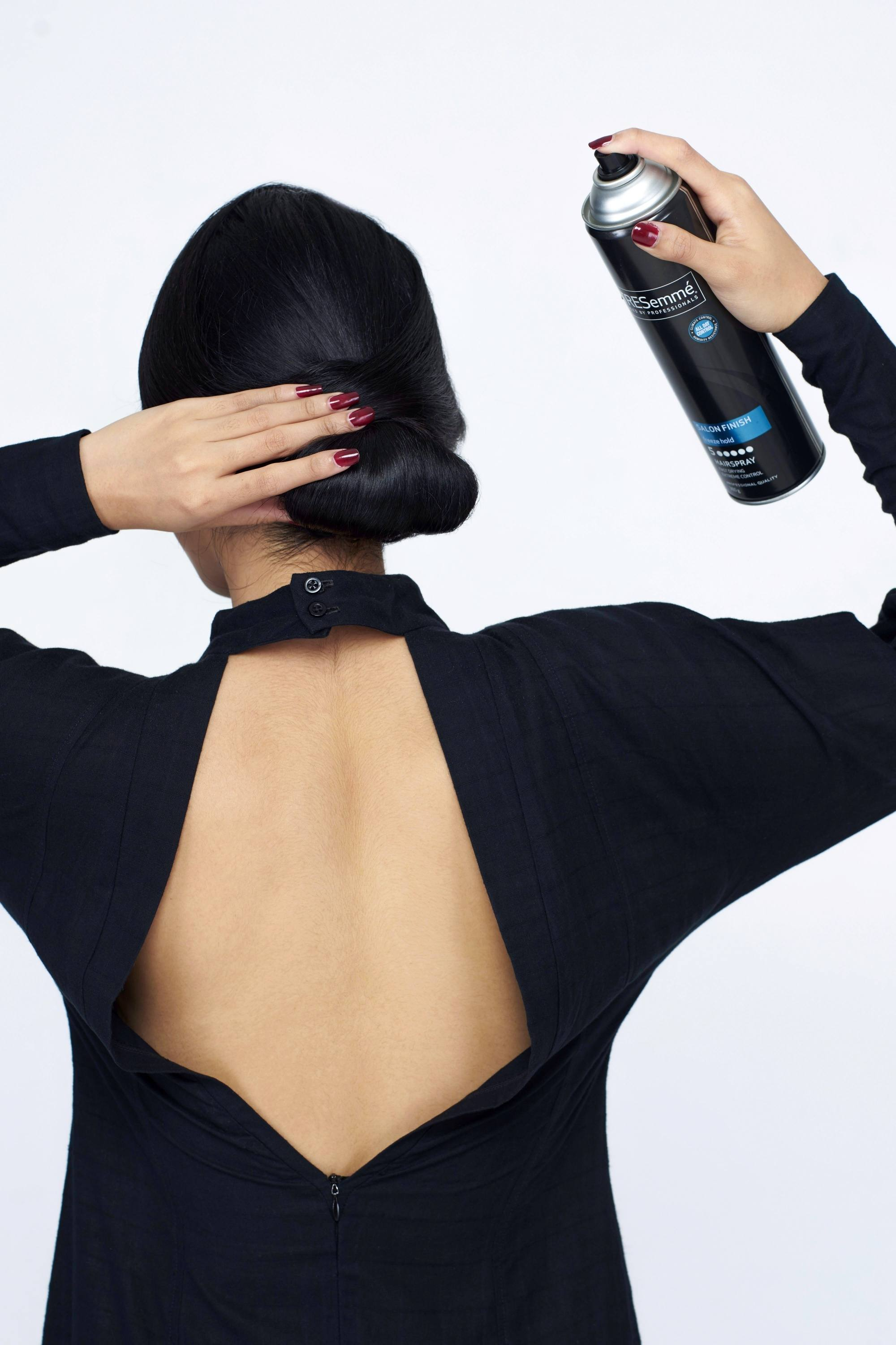 Hair spray guide: Back of Asian woman spraying on her black chignon hair