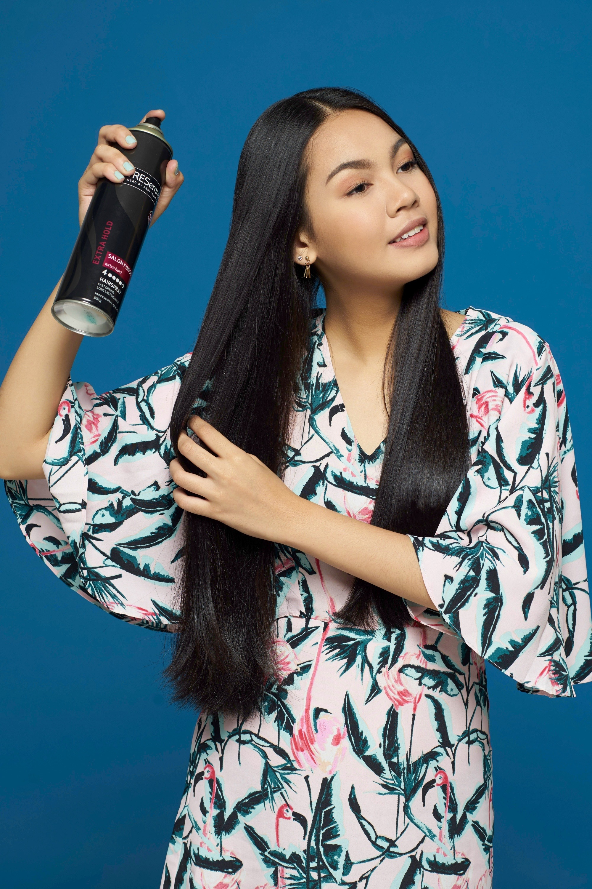 Hair spray guide: Asian woman spraying on her long black hair