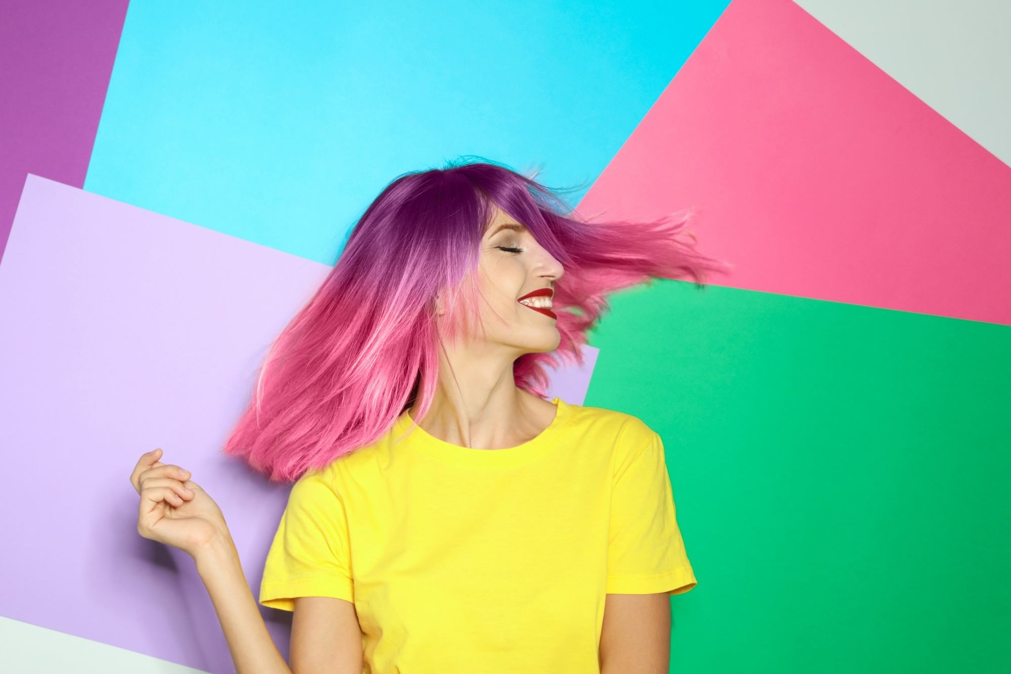 How often should you change your hair color: Woman with shoulder-length pink ombre hair wearing a yellow shirt against a colorful background