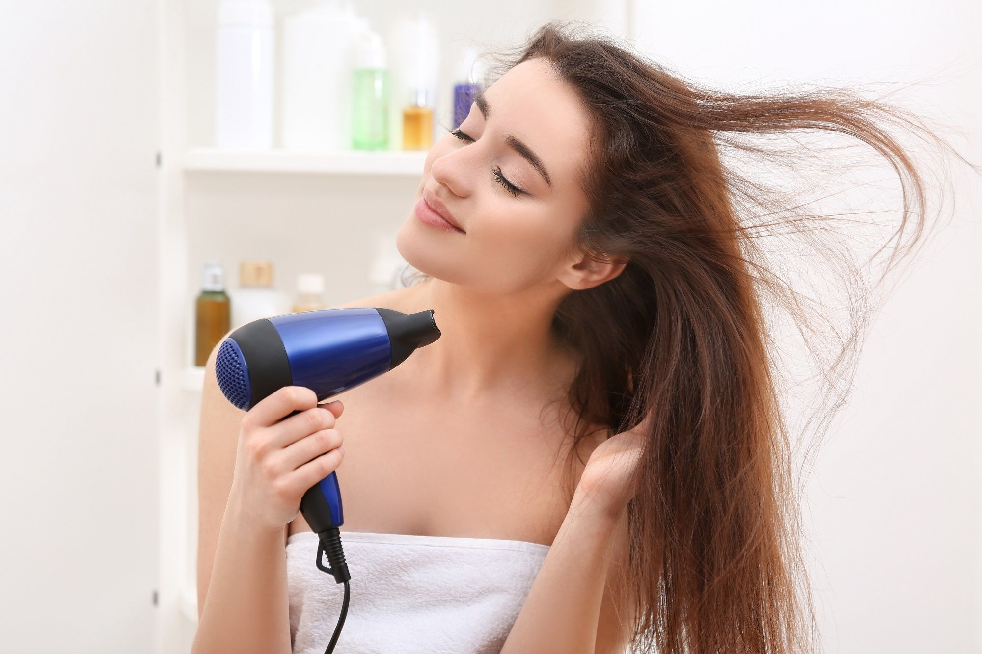 How to get beautiful hair: Closeup shot of a woman wrapped in a white towel blow drying her long brown hair