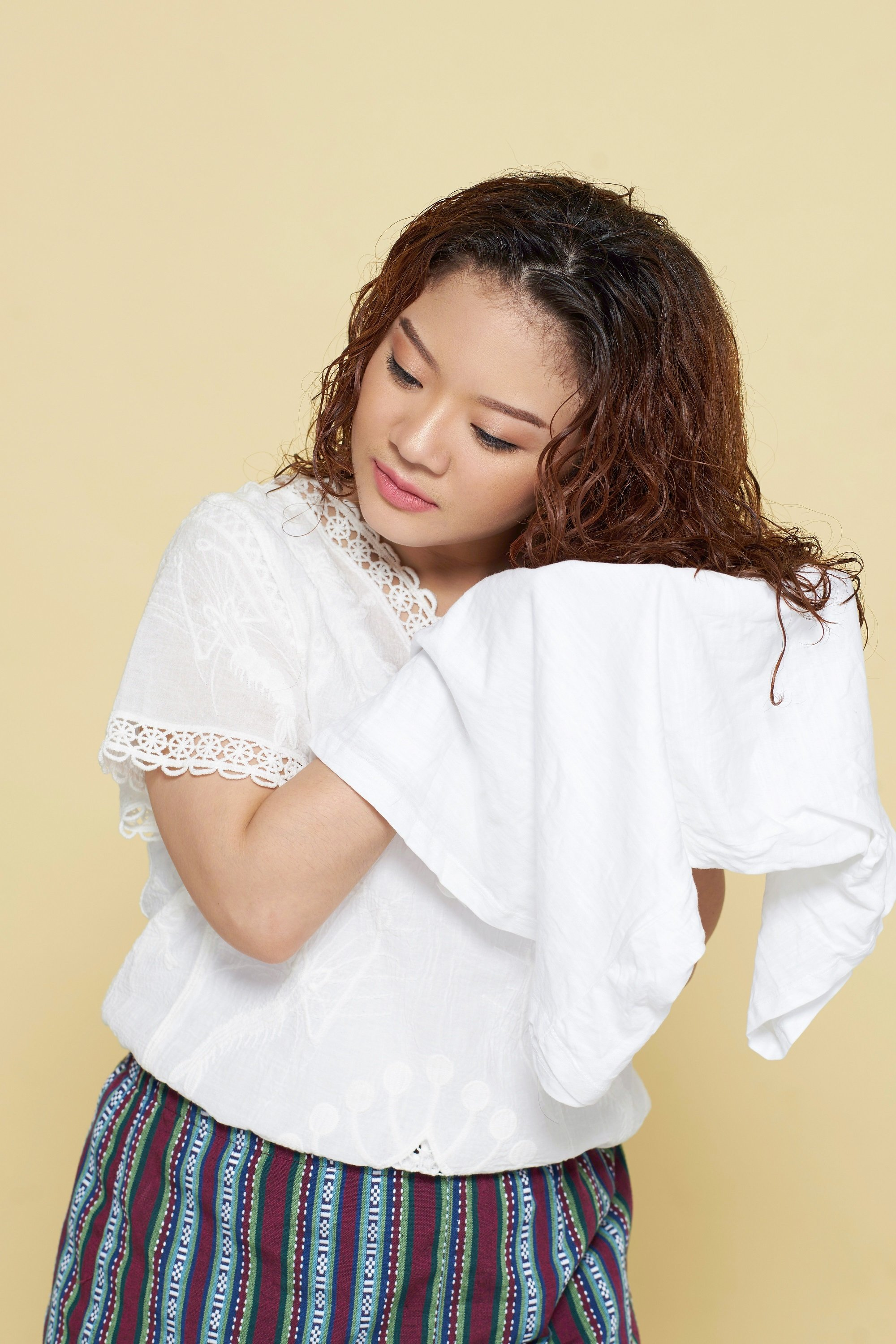 How to get beautiful hair: Asian woman squeezing her long curly hair with a white shirt