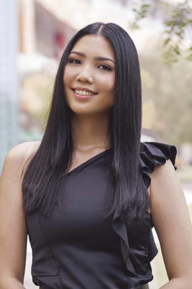How to get beautiful hair: Asian woman wearing a black one-shoulder top with long black hair in a park outdoors