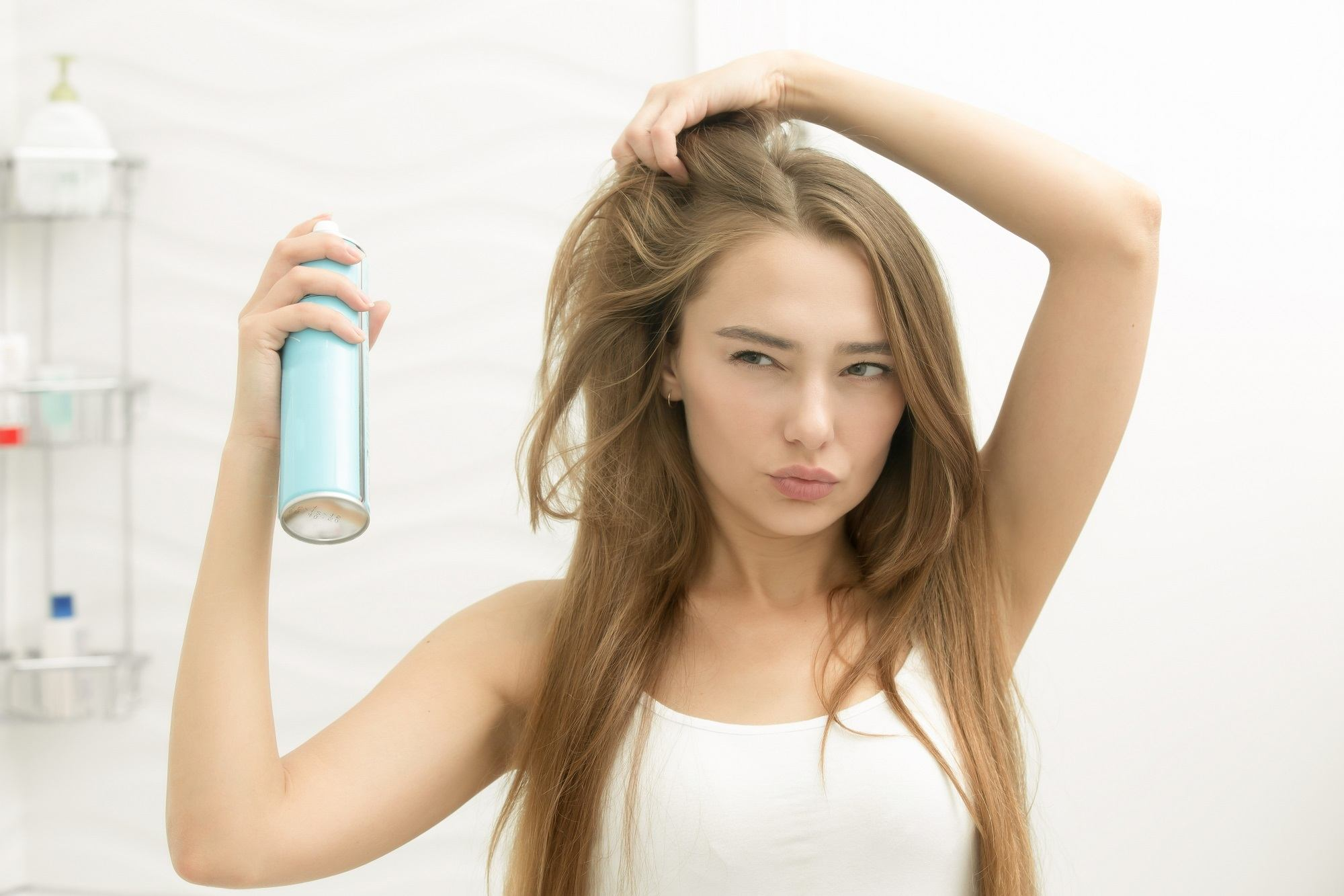How to get beautiful hair: Woman wearing a white tank top spraying on her long brown hair