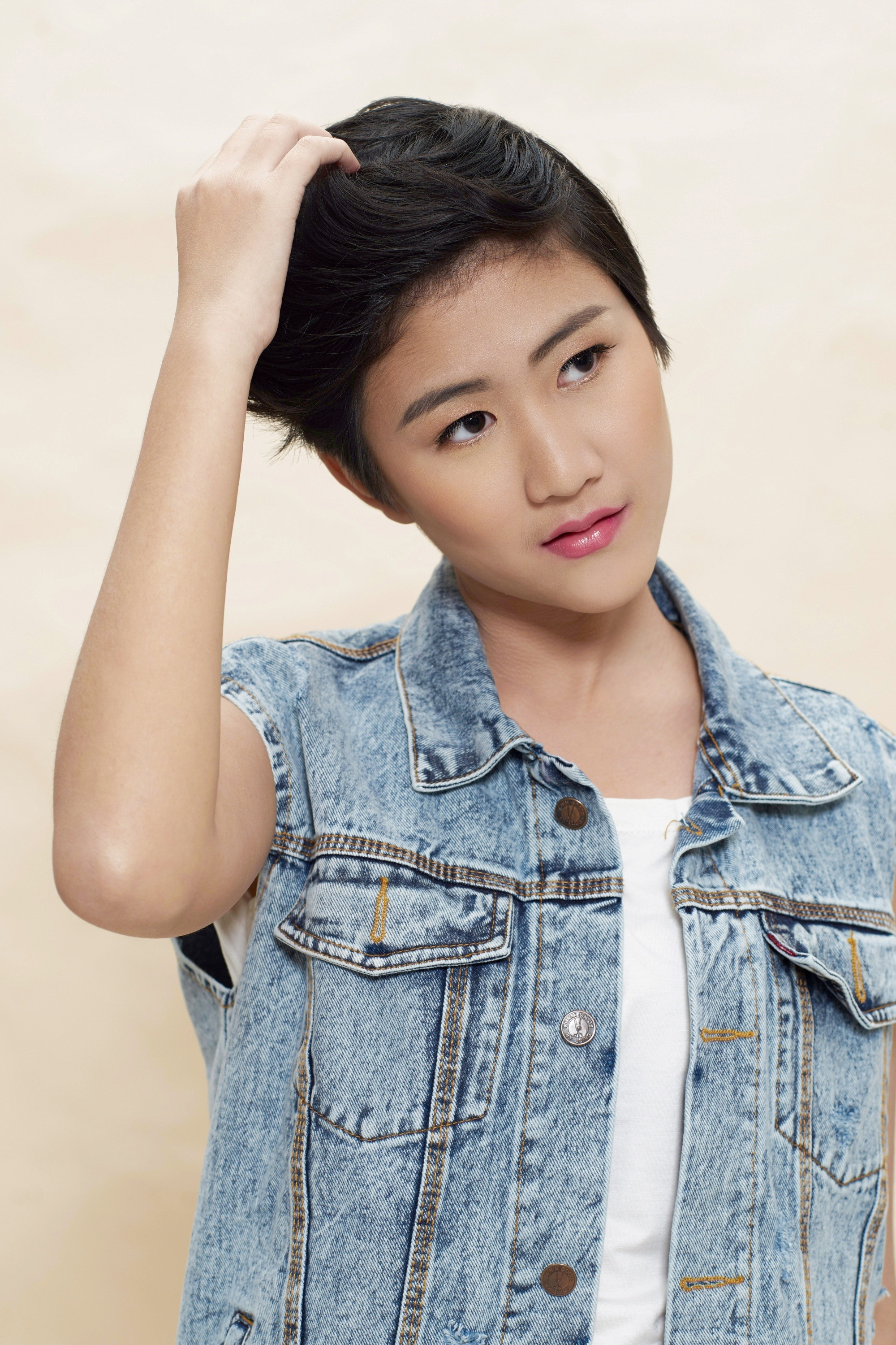 How to use hair wax: Asia woman with short black pixie cut wearing a denim vest touching her hair