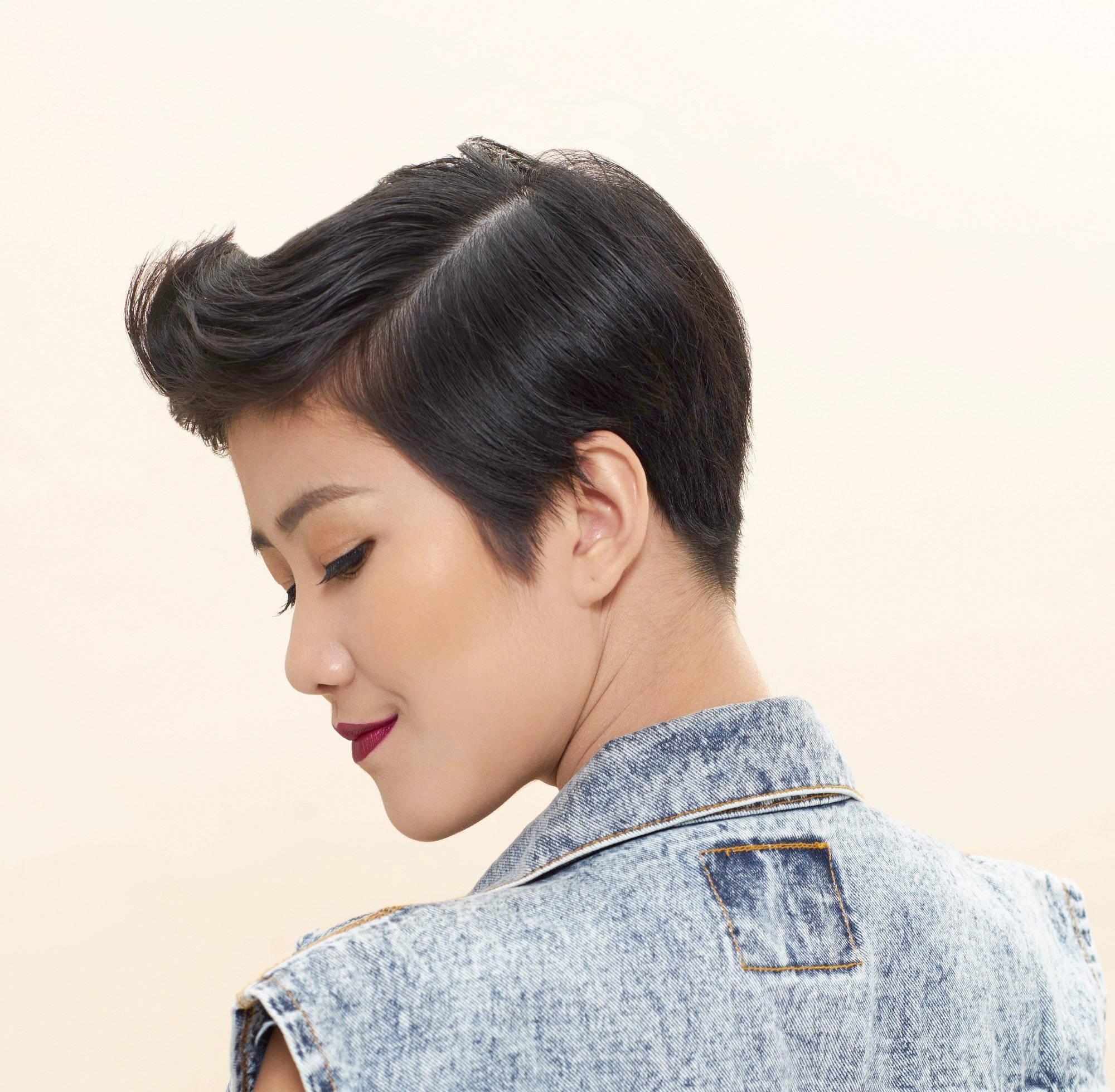 How to use hair wax: Closeup shot of an Asian woman with black pixie cut wearing a denim vest