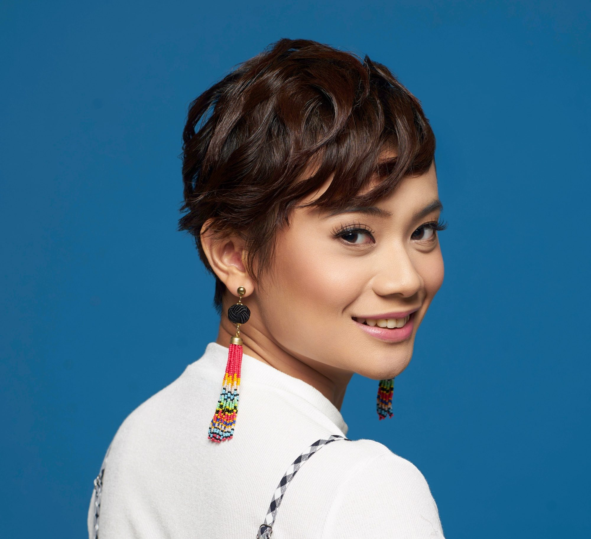 How to use hair wax: Closeup shot of an Asian woman with short dark pixie cut wearing a white shirt and long earrings