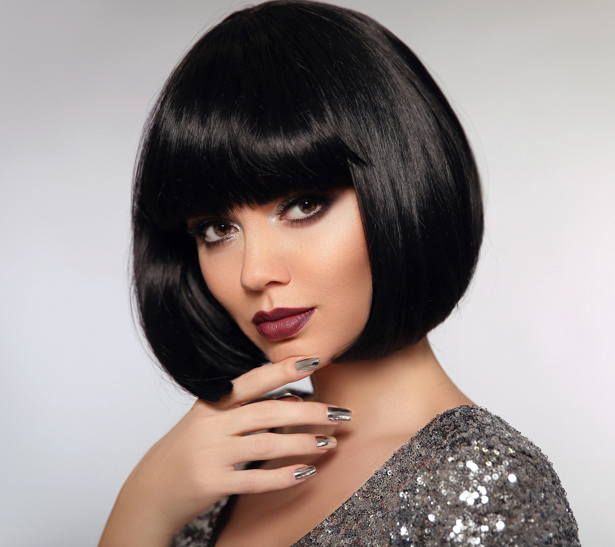 Short hair for round face: Closeup shot of a woman with short black hair and blunt bangs