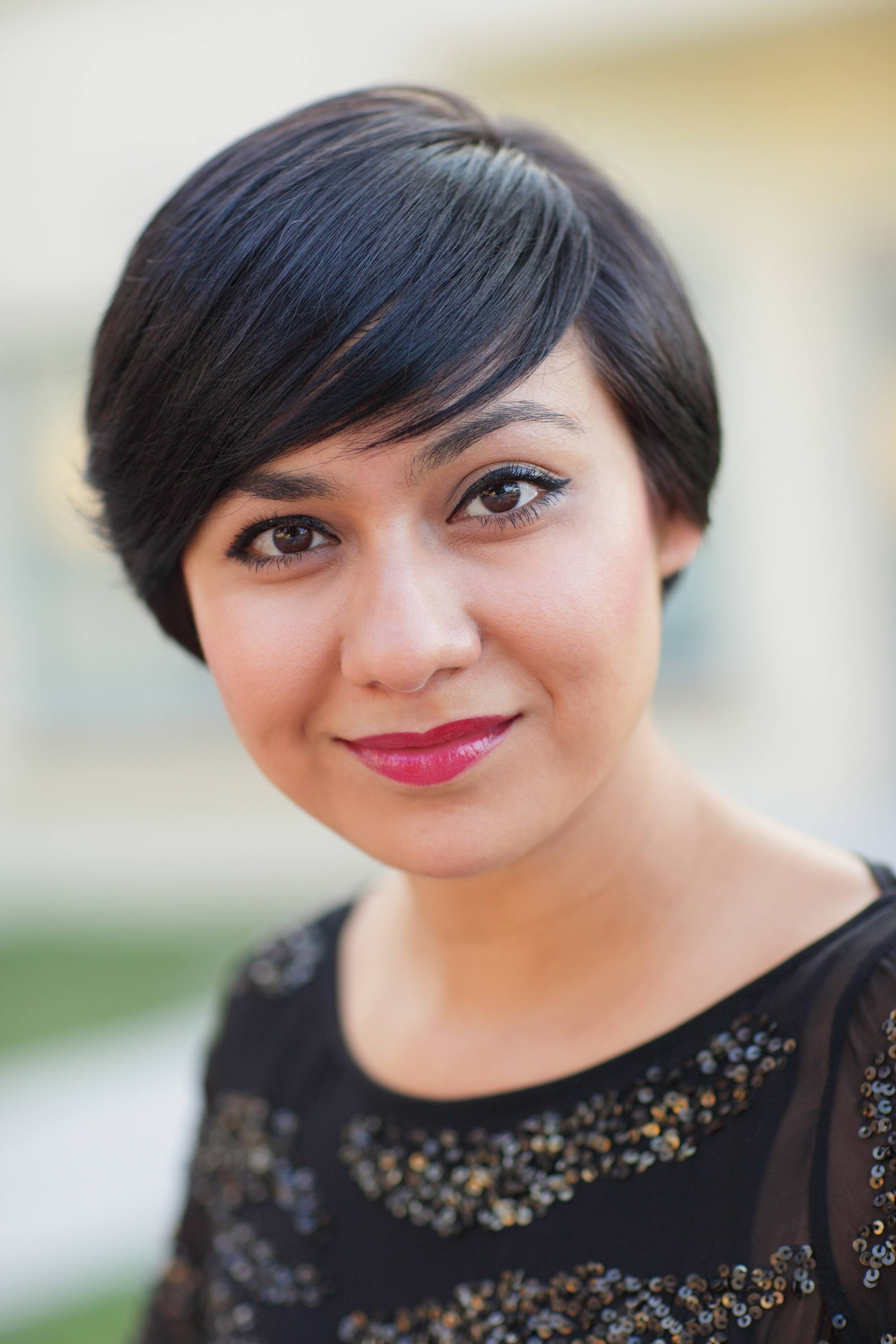 Short hair for round face: Closeup shot of a woman with short dark hair with side swept bangs