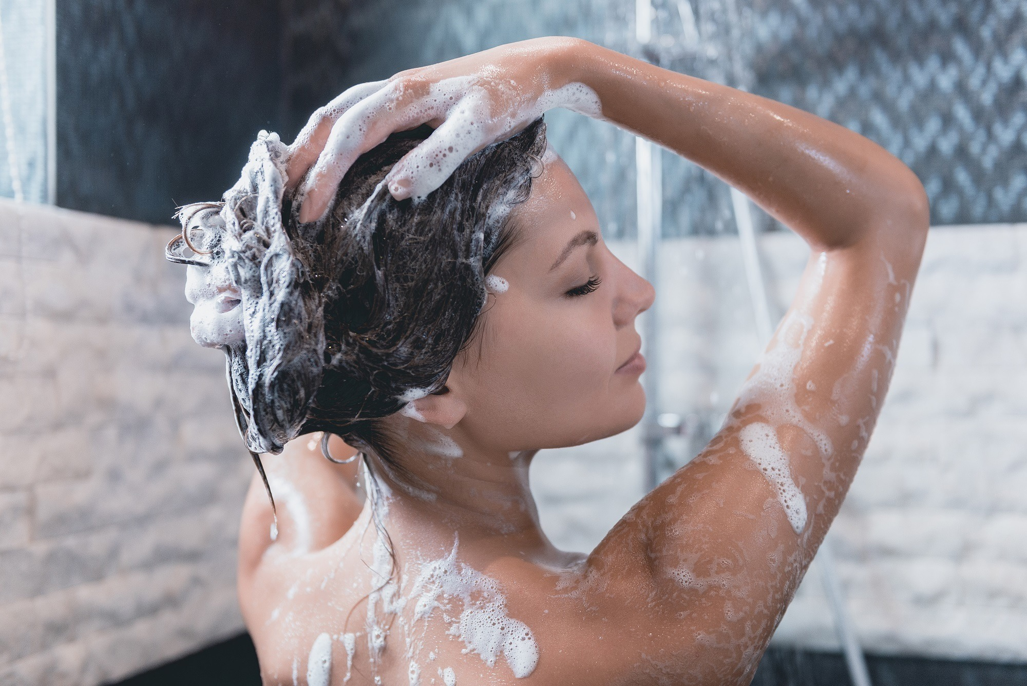 Frizzy hair remedies: Closeup shot of a woman shampooing her hair in the shower