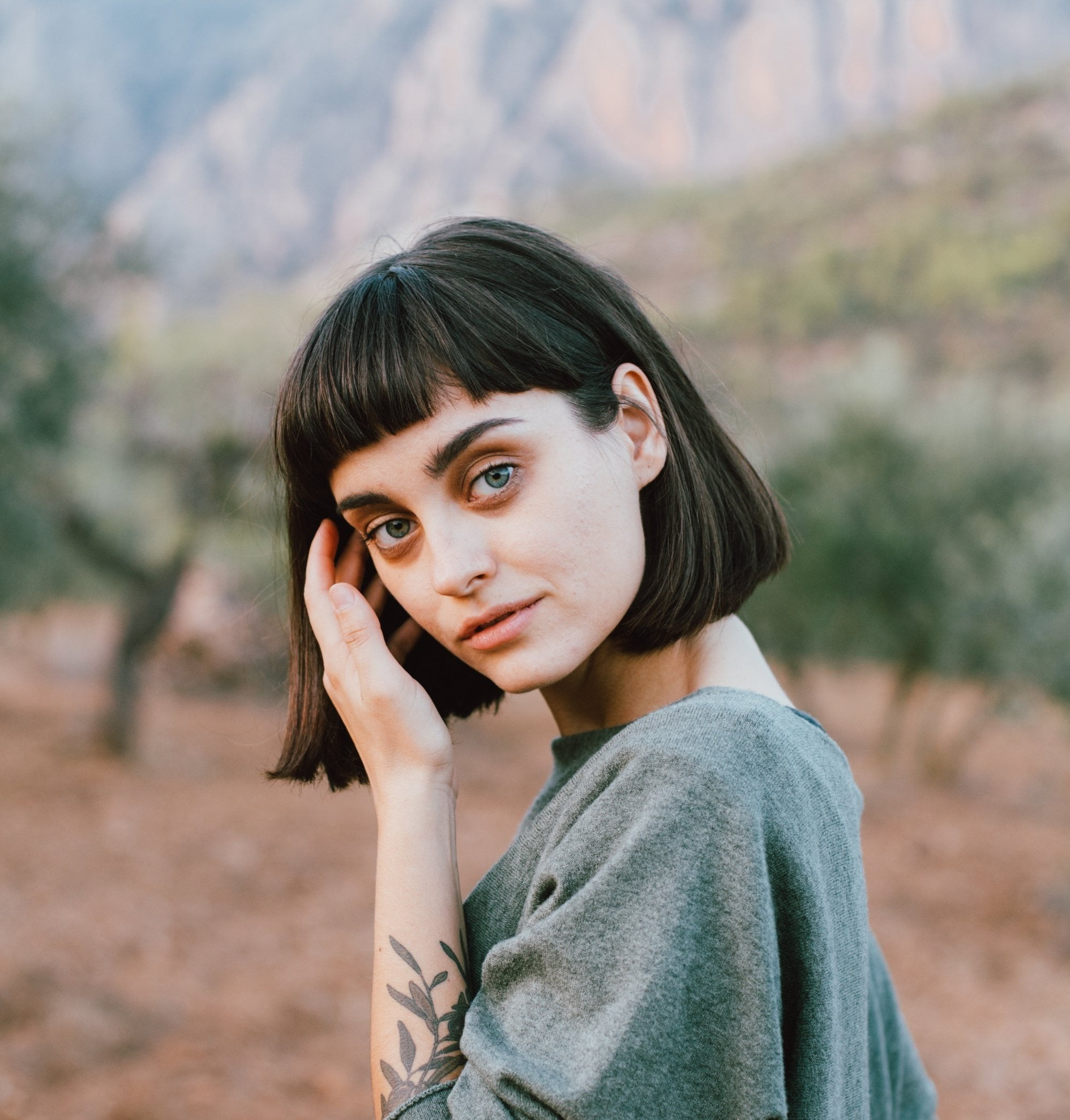 Styling blunt bangs: Closeup shot of a Russian woman with short black hair with baby bangs standing in the woods