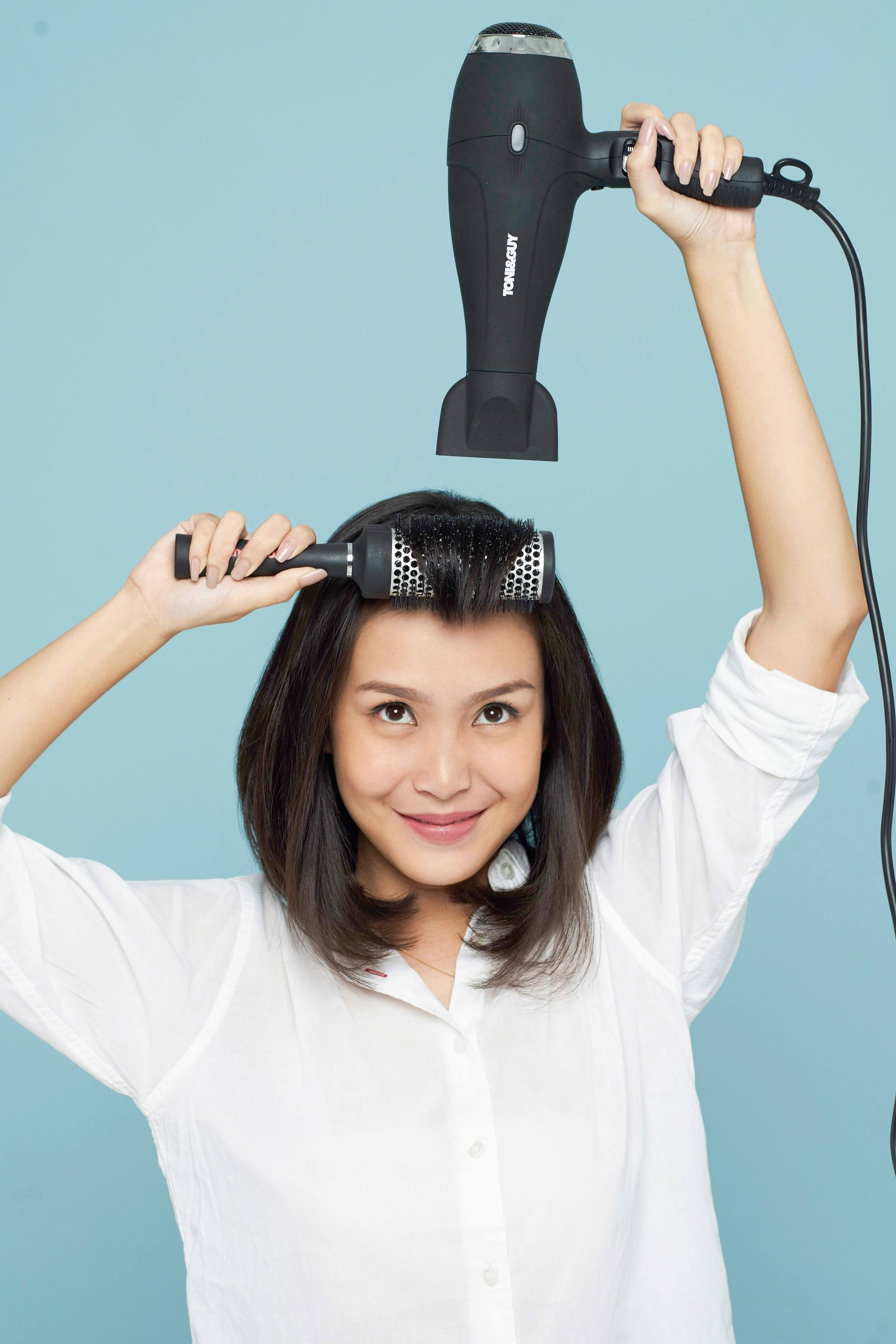 Styling blunt bangs: Asian woman with black hair blow drying her bangs