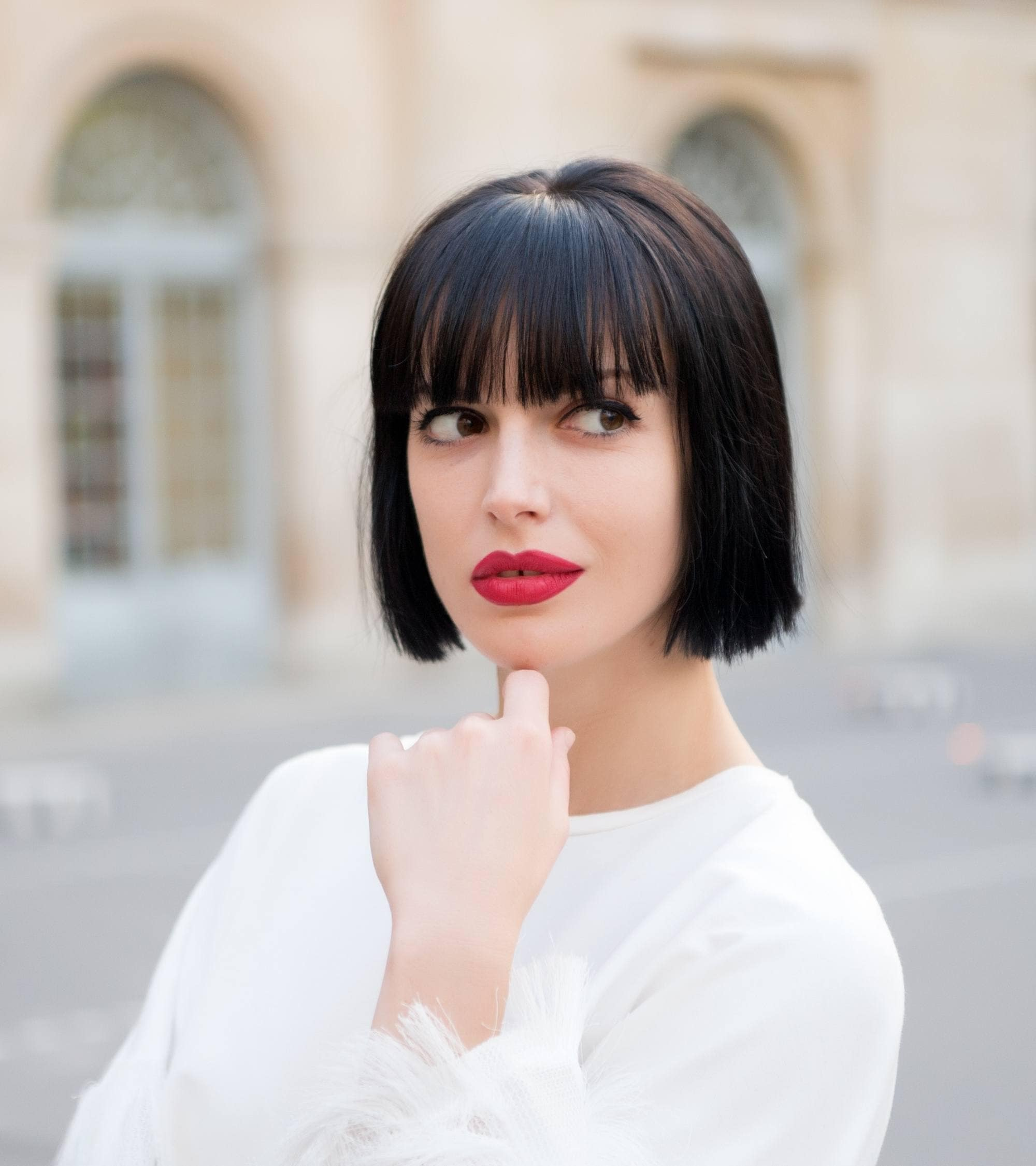 Styling blunt bangs: Closeup shot of a woman with short black hair with blunt bangs wearing a white top outdoors