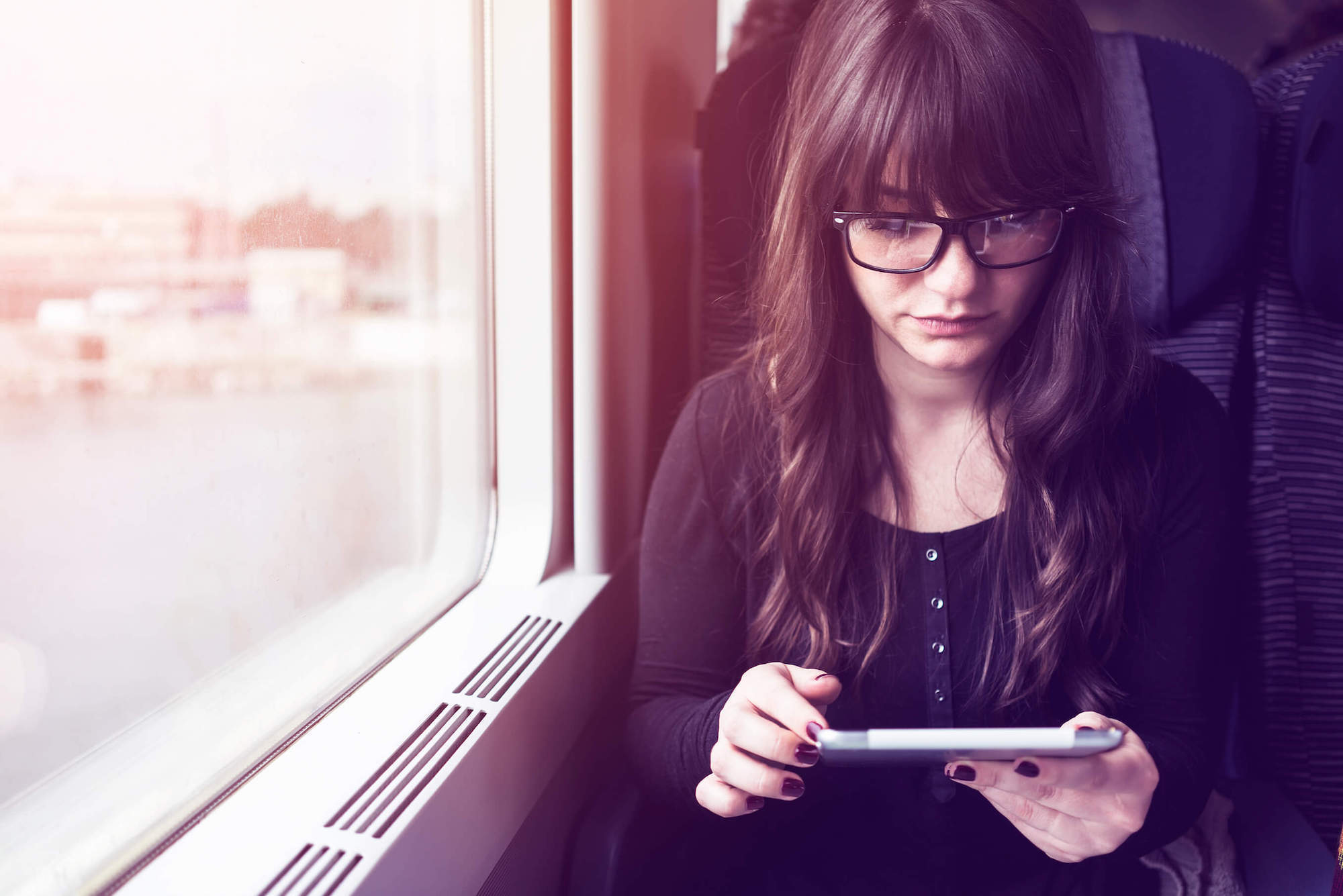Should I get bangs: Girl on a train with long dark hair and blunt bangs with eyeglasses reading on her tablet