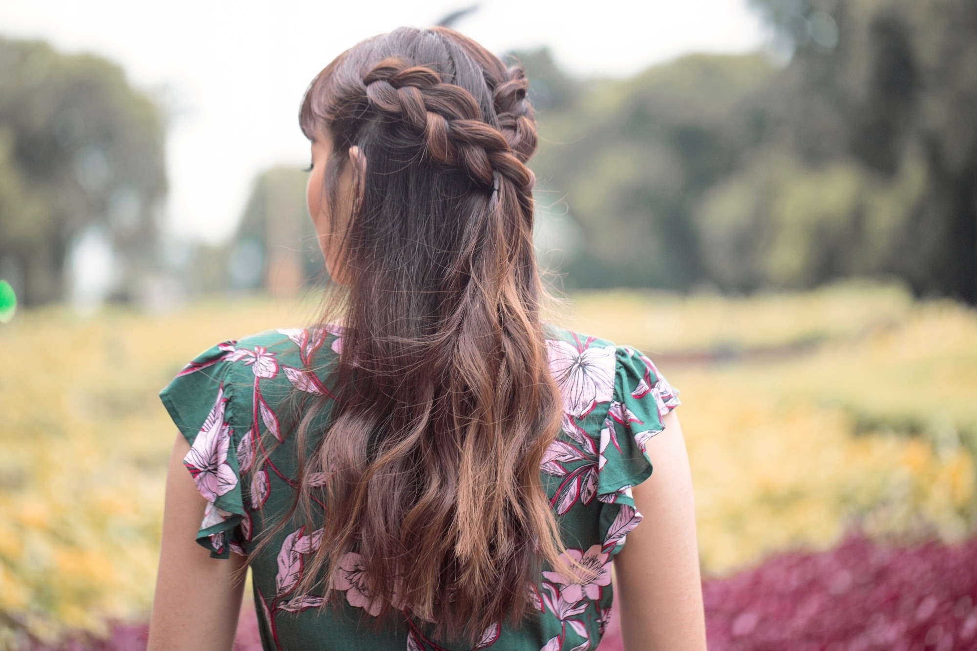 Bridal hairstyle: Back shot of an Asian woman with long dark hair in half up boho braid wearing a dress outdoors