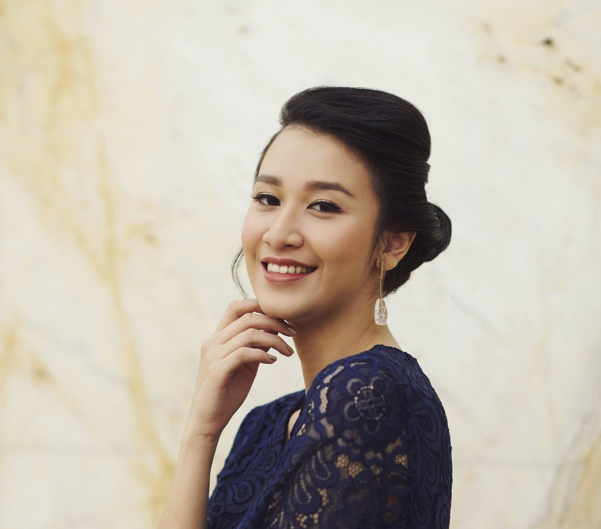 Bridal hairstyle: Closeup shot of an Asian woman with dark hair in a low bun wearing a blue dress outdoors