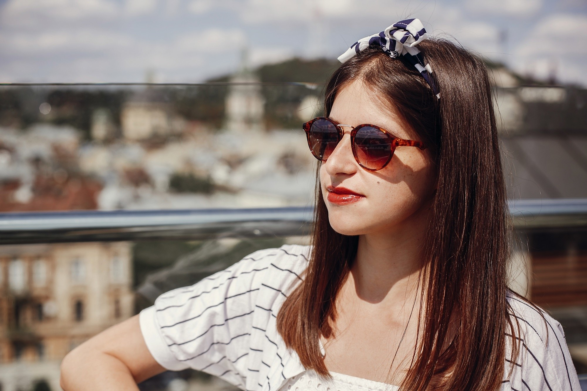 Hair care tips for traveling: Closeup shot of a woman with long dark hair wearing shades and a headband