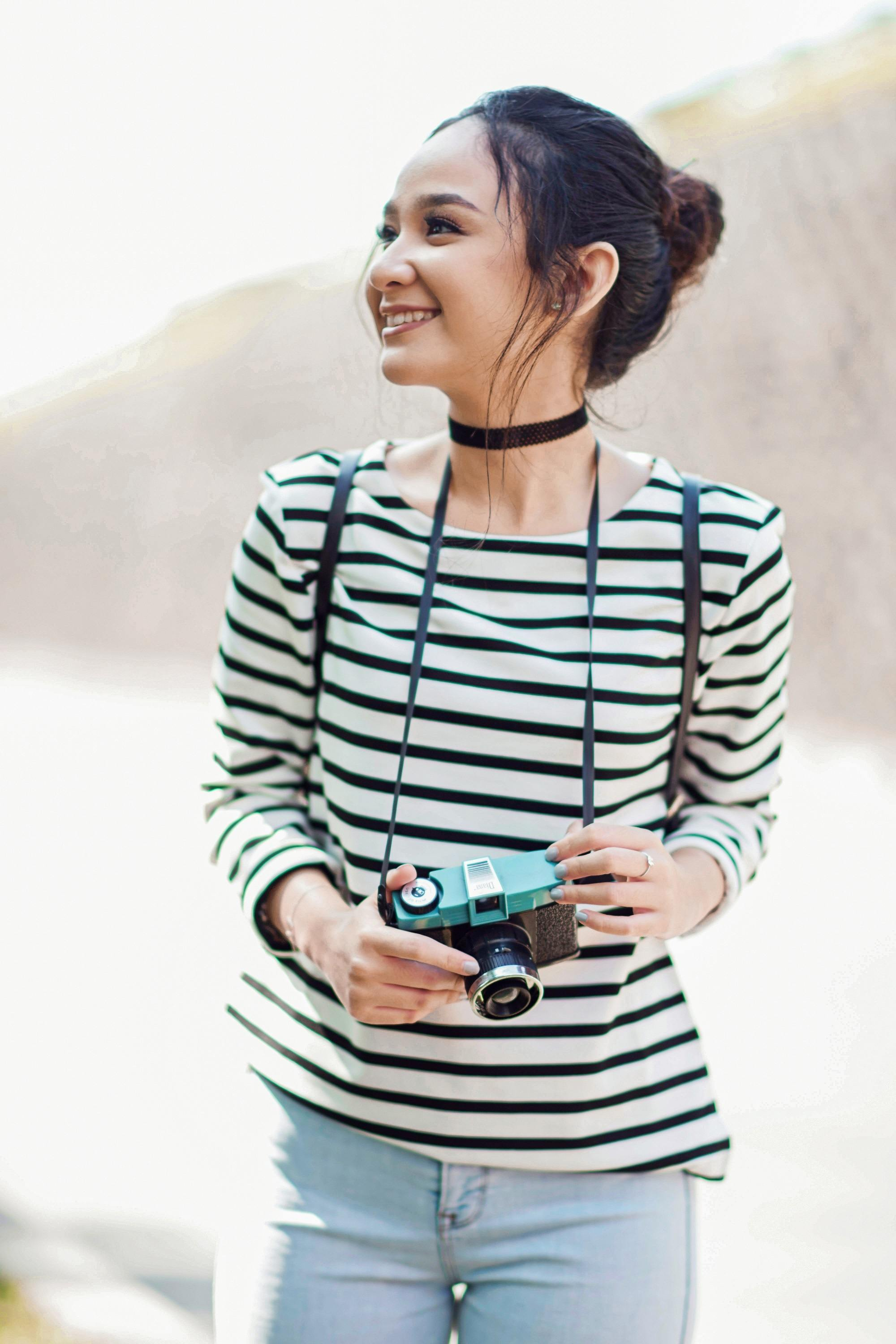 Hair care tips for traveling: Asian woman with long hair in a bun wearing striped shirt and denim jeans outdoors