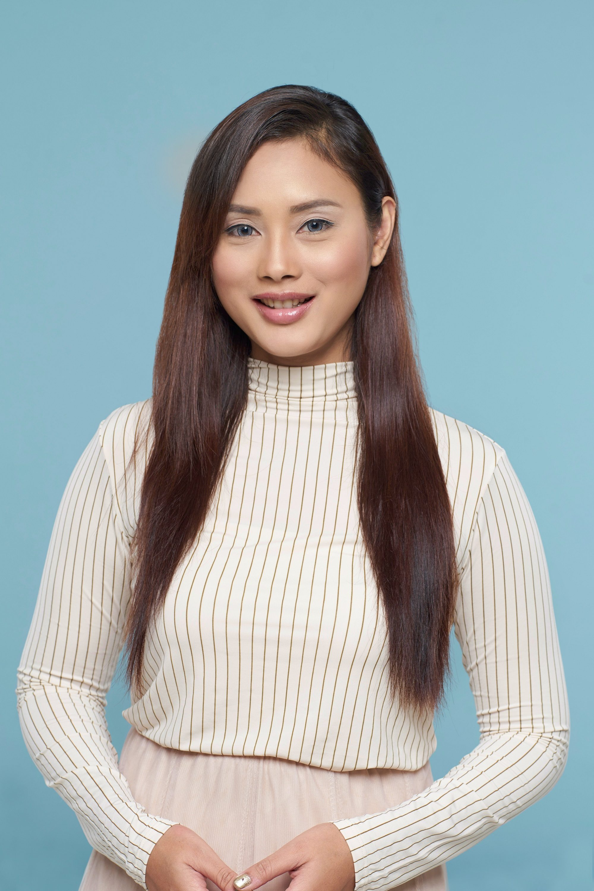 How to use leave-in conditioner: Asian woman with long dark hair wearing a white long-sleeved top
