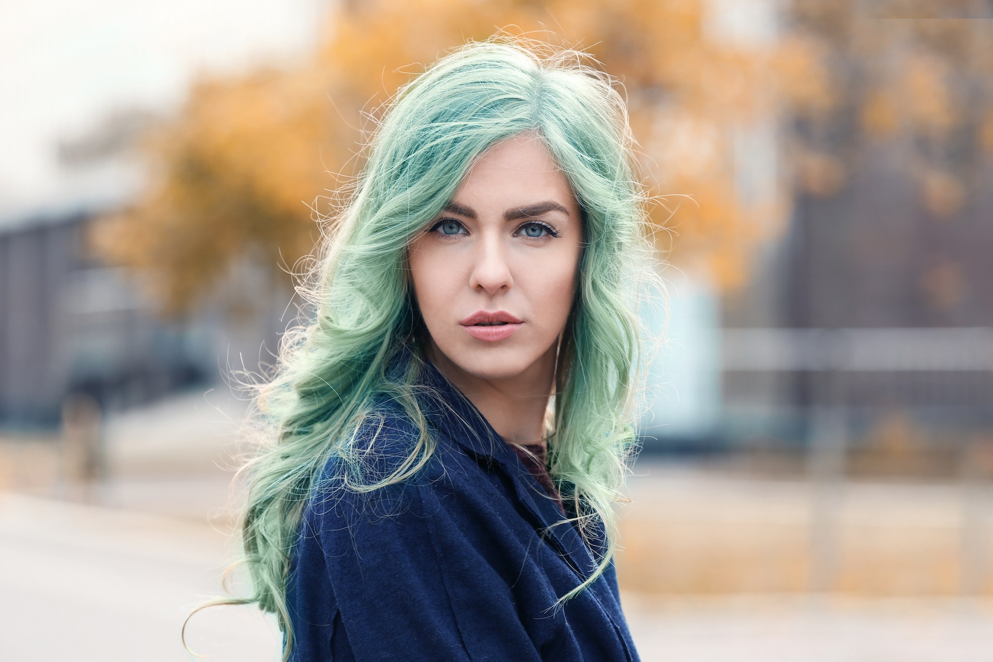 Pastel hair colors: Caucasian woman with long mint green hair wearing a blue sweater outdoors