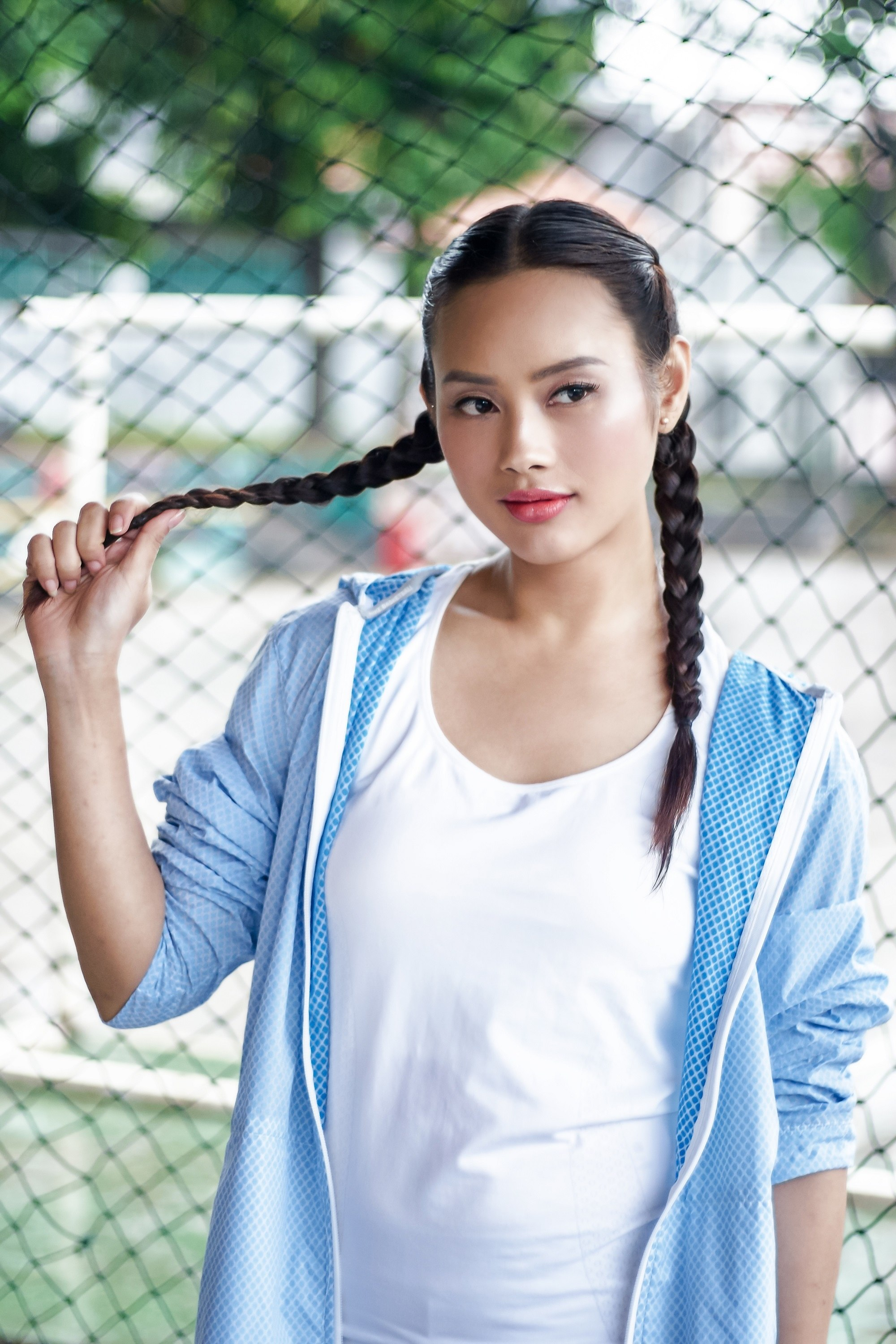 Easy commuter-friendly hairstyles: Asian woman with long black hair in boxer braid wearing a blue sweater outdoors