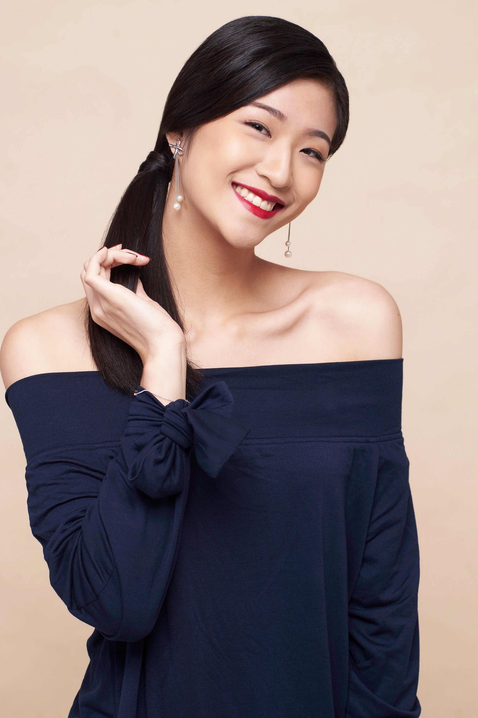 Easy commuter-friendly hairstyles: Asian woman with long black hair in a side ponytail wearing a dark blue off-shoulder top