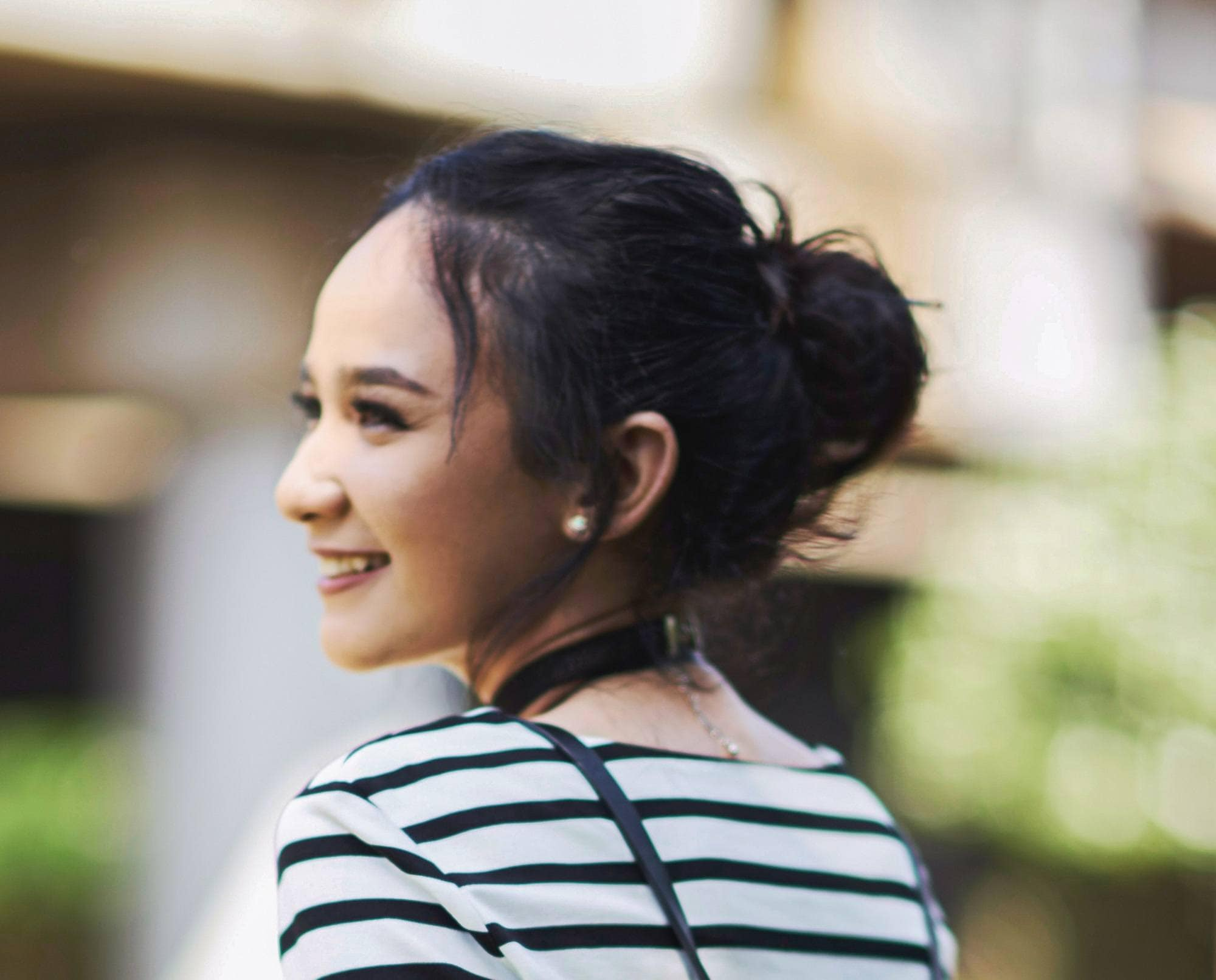 Easy commuter-friendly hairstyles: Closeup shot of an Asian woman with black hair in a messy bun wearing striped shirt outdoors