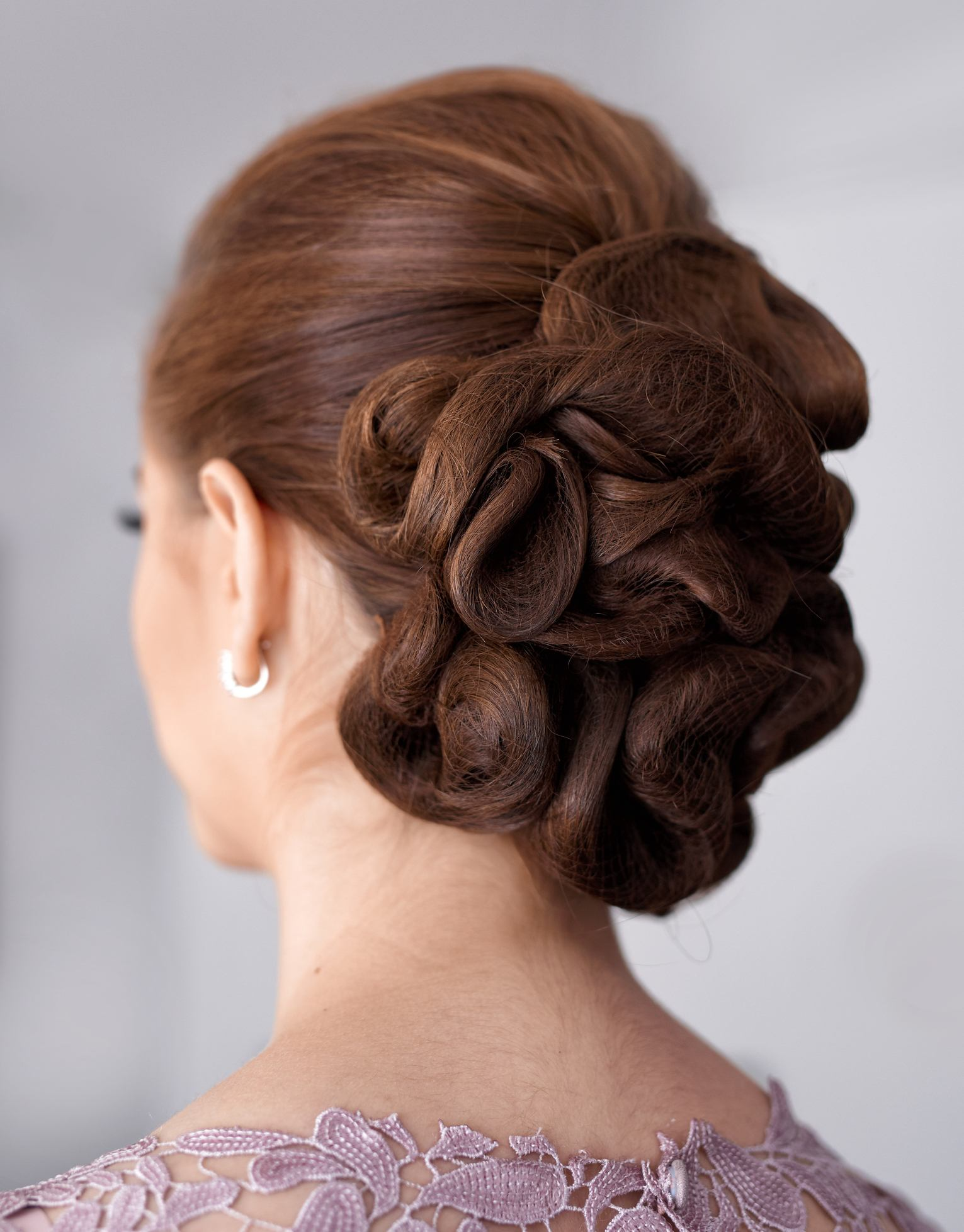 rear view of prom updos with elegant woman with amazing hair bun, hairstyle background.