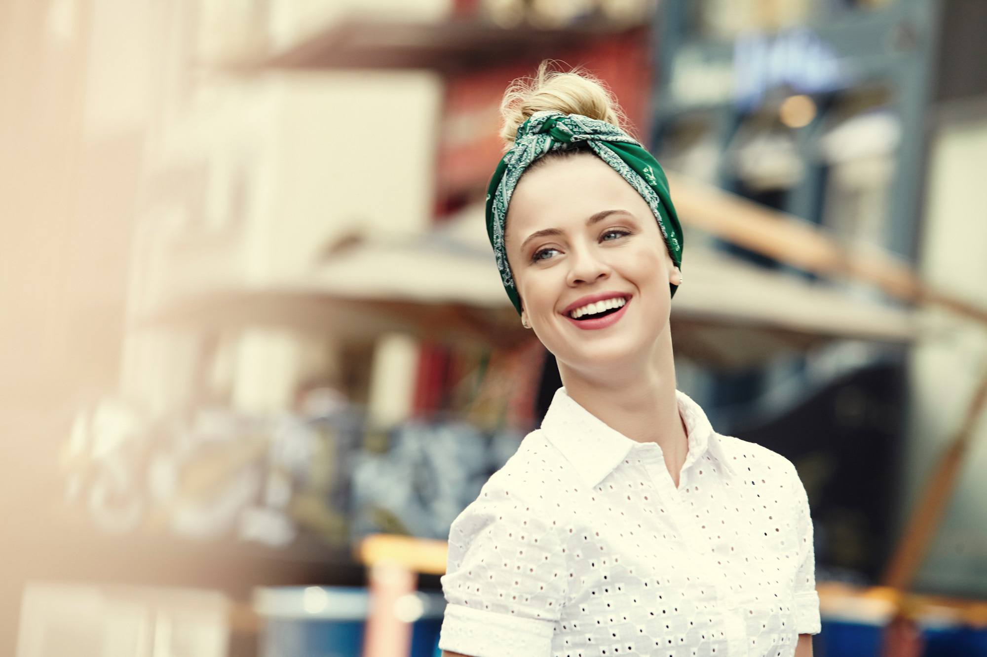 Easy commuter-friendly hairstyles: Blonde woman with a bun and bandanna wearing a white blouse outdoors