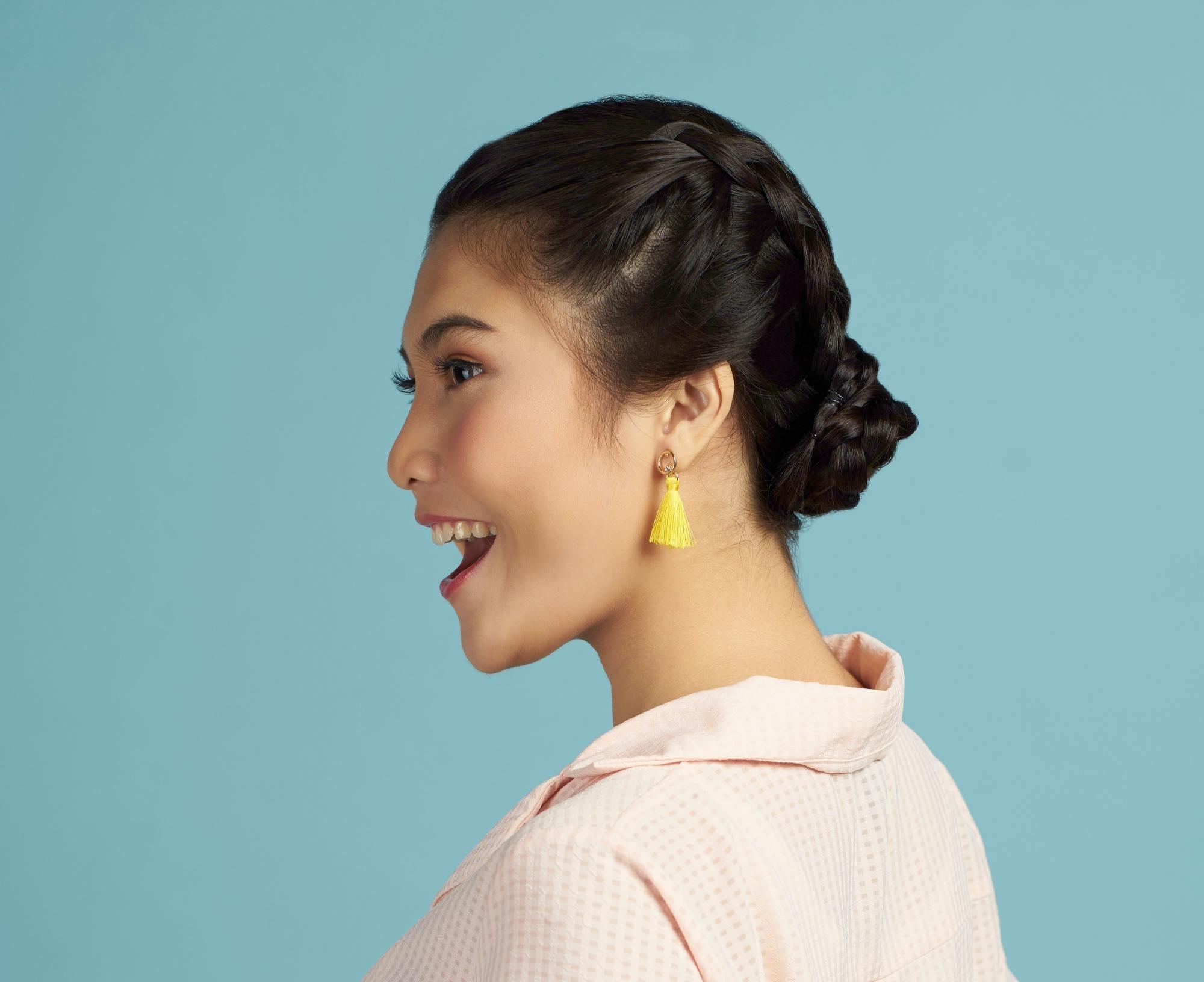 Closeup shot of an Asian woman with black hair in Double Dutch braid bun