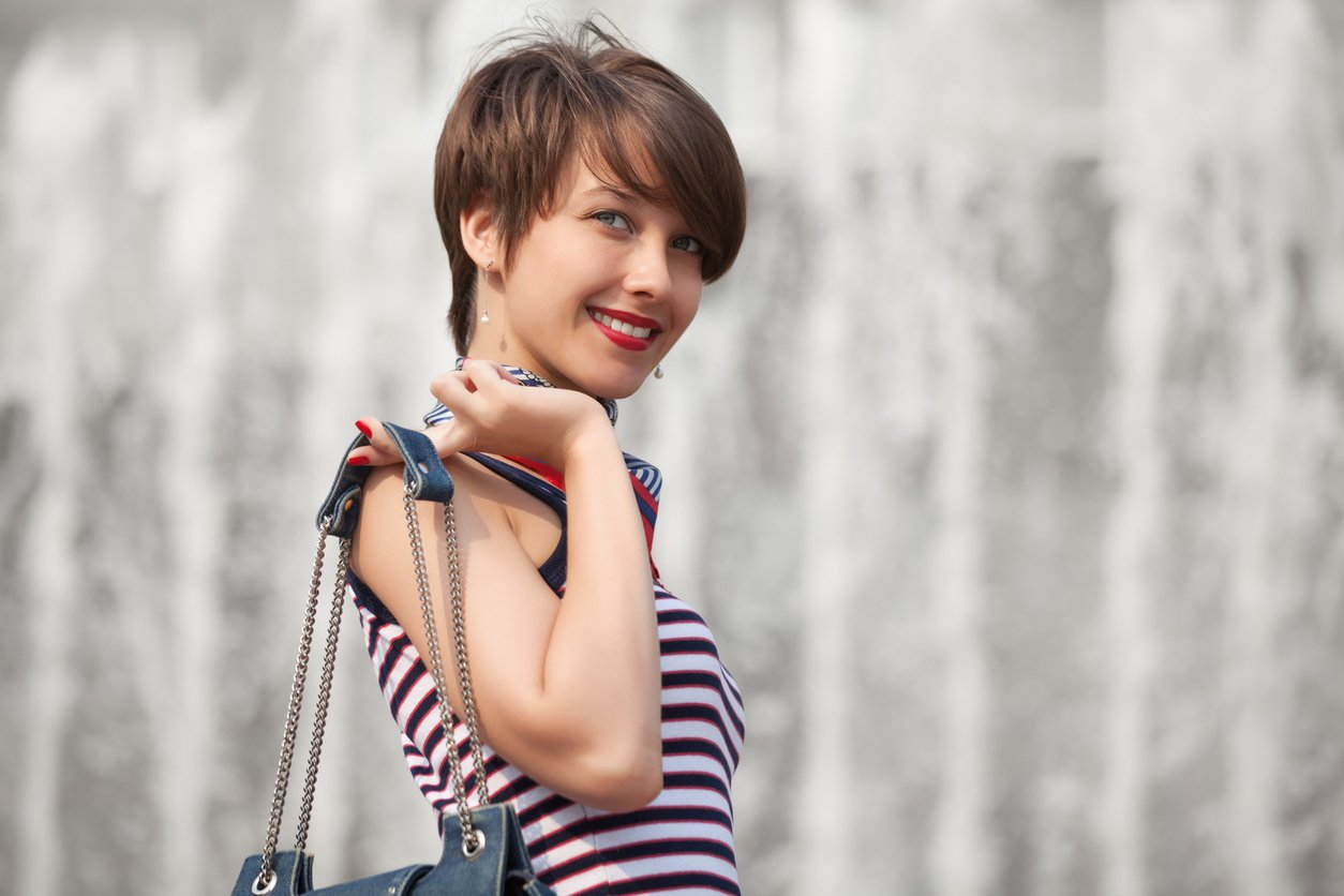 Happy young fashion woman with handbag and short hairstyles walking outdoor