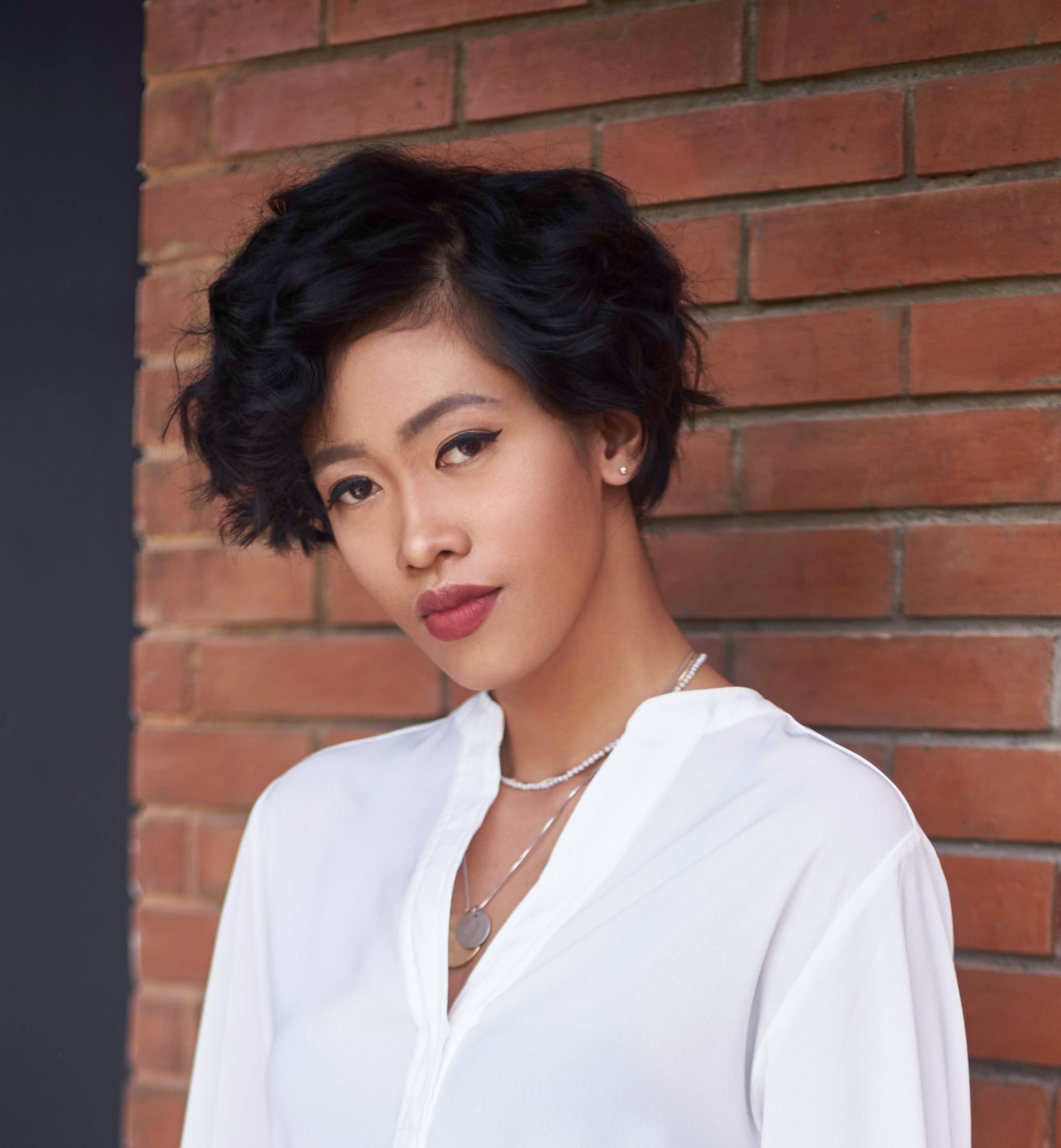 Short hairstyles for Filipinas: Closeup shot of an Asian woman with curly short hair black hair wearing a white top