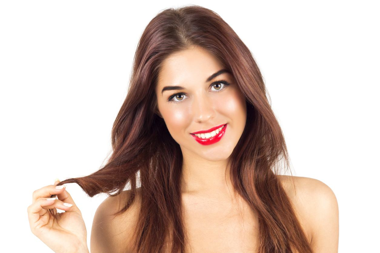 Tanned woman with red lips. Tanned woman playing with burgundy color hair.