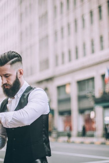 Retro looking businessman with hard part haircut going through the town dressed in formal wear, checking the time.