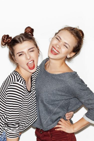 Two young girls taking pictures. Double bun and messy top knot hairstyle.