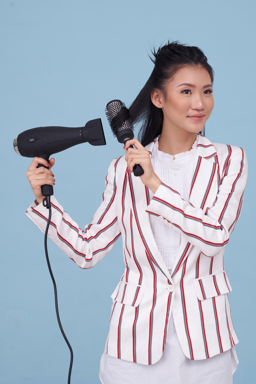 Blow dry your hair: Asian woman blow drying and brushing her medium-length dark hair