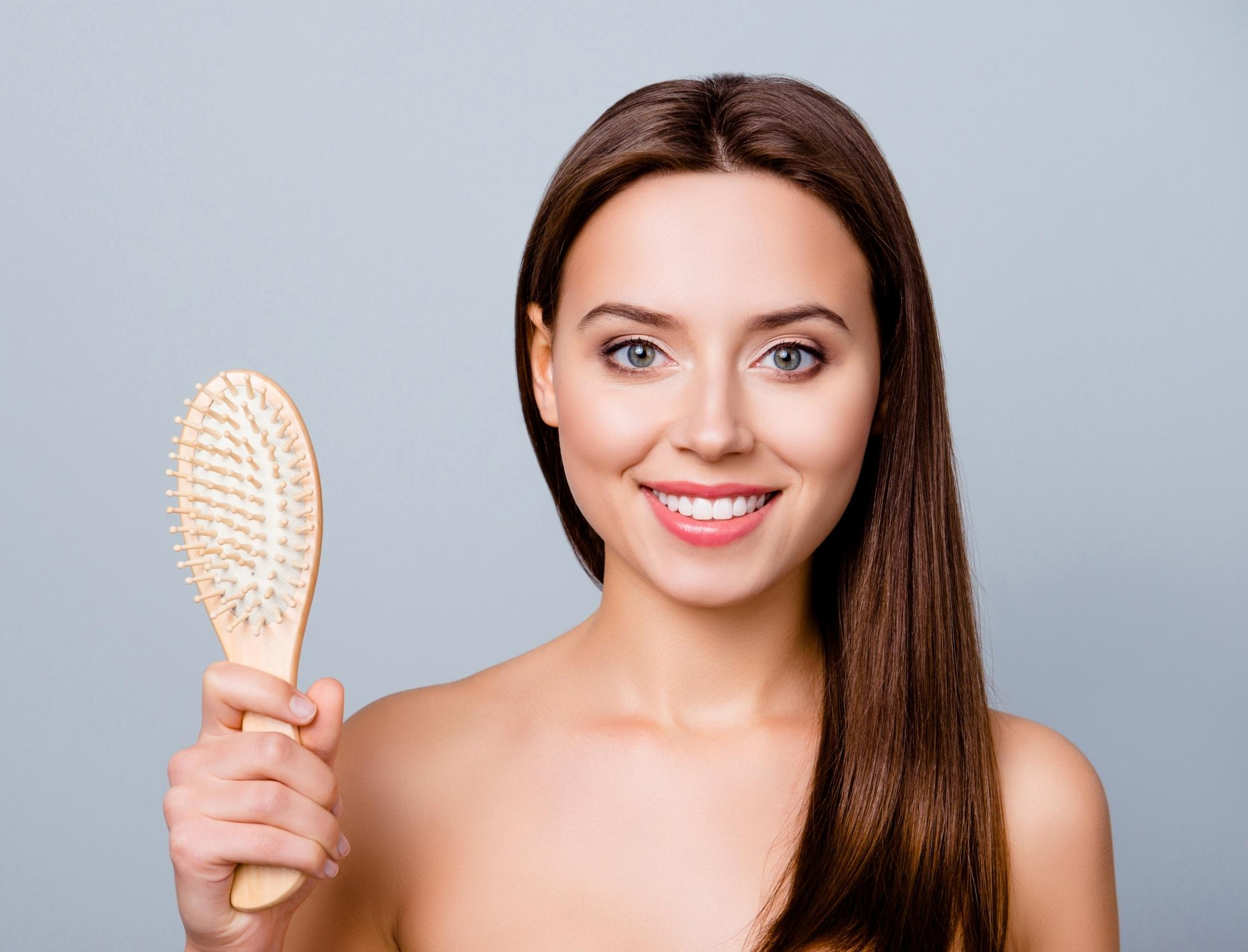 Brush your hair the right way. Woman with long straight dark brown hair holding a hairbrush
