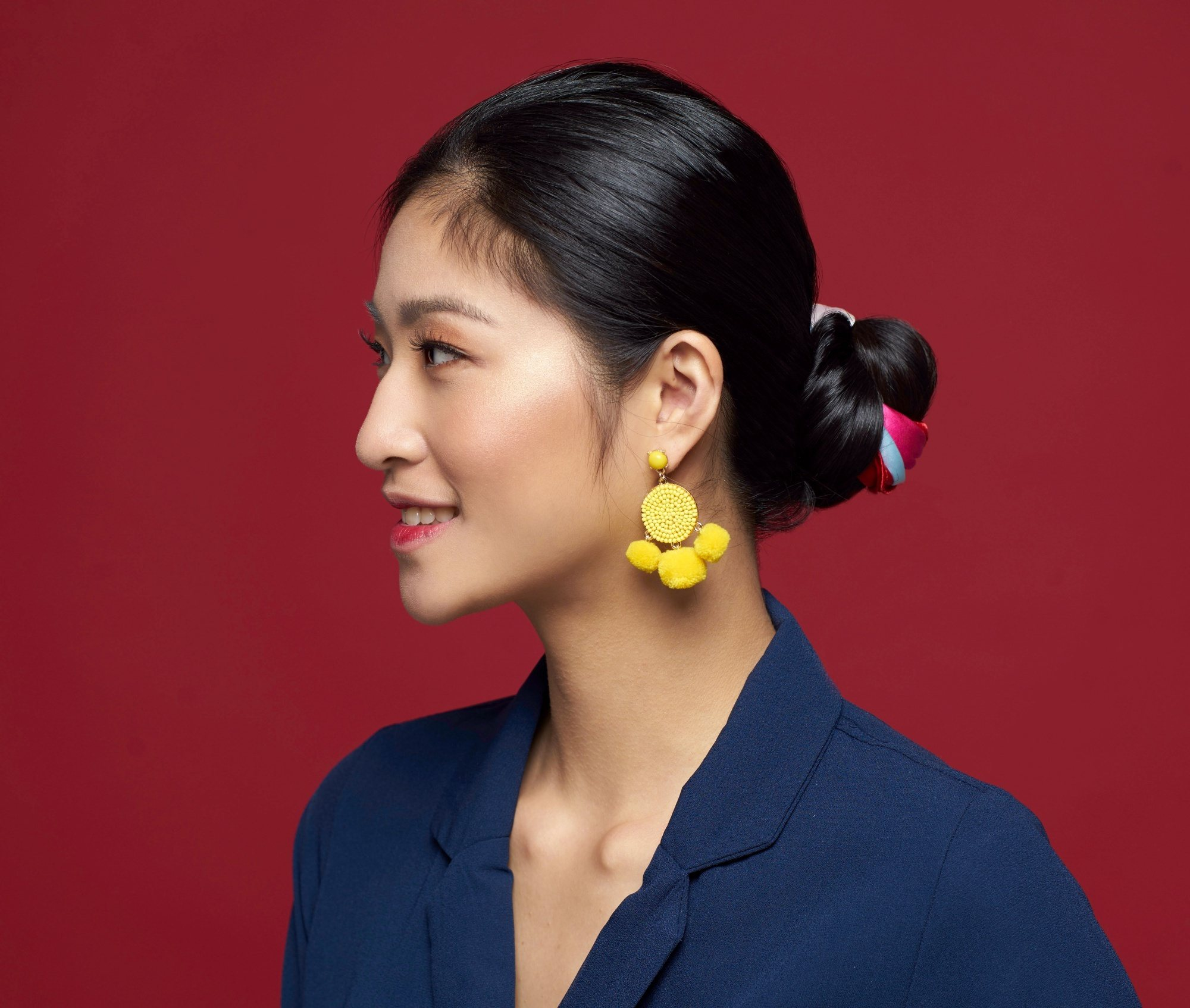Casual hairstyles: Closeup side view of an Asian woman with long black hair in a scarf bun wearing a blue blouse
