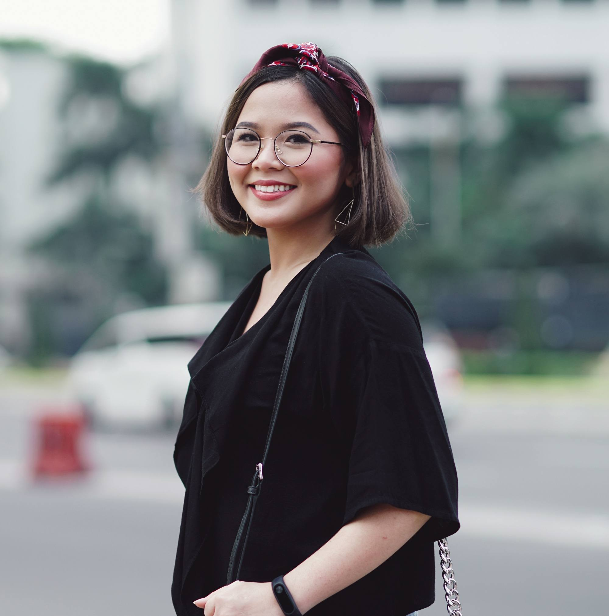 Chin length hairstyles: Asian woman with short dark hair with headband wearing eyeglasses and a black shirt